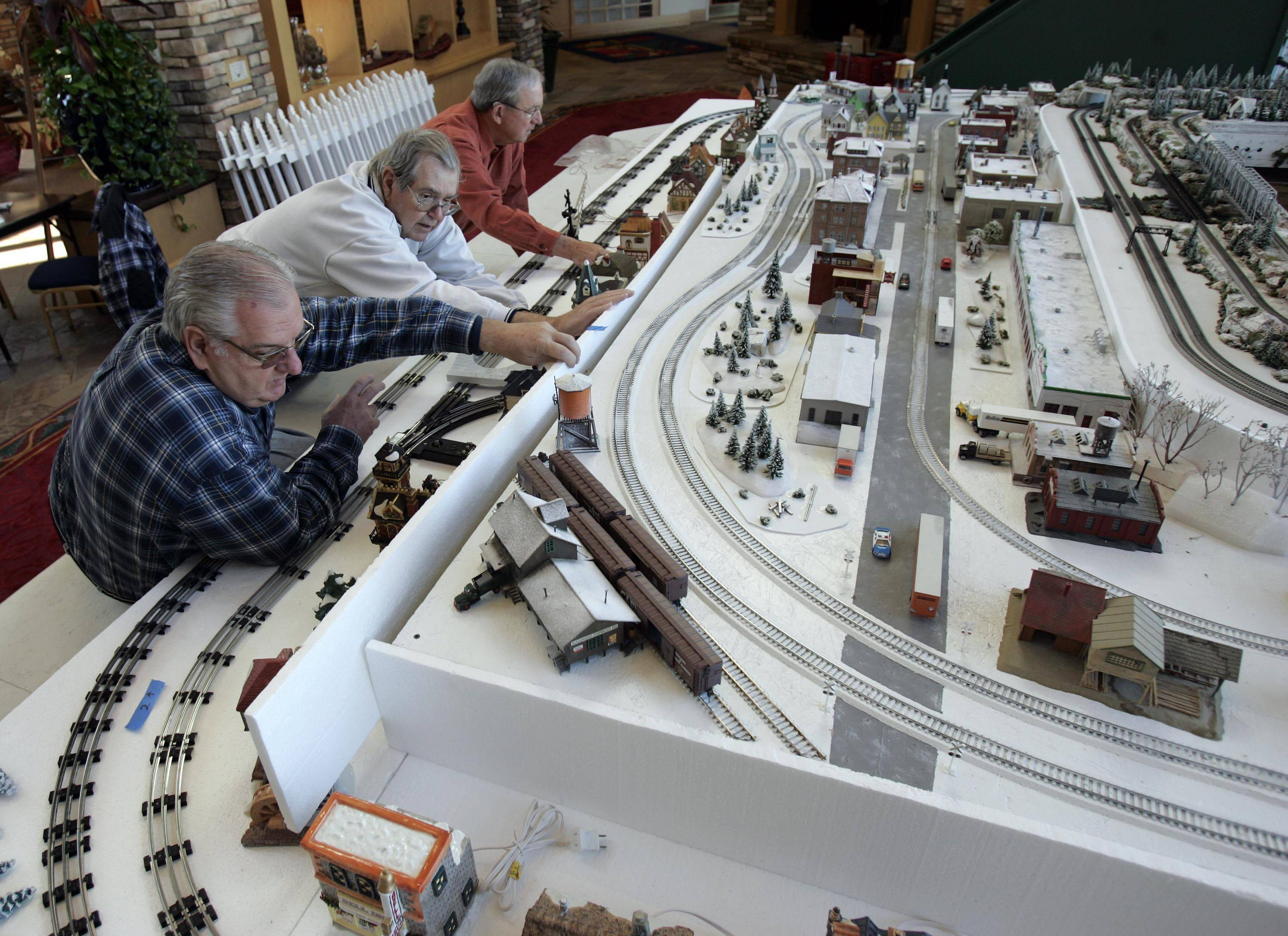 Sun City residents Paul Strokosch, from left, Ed Kopp, and Pete Walton work to set up the trains Tuesday, November 23, 2010.