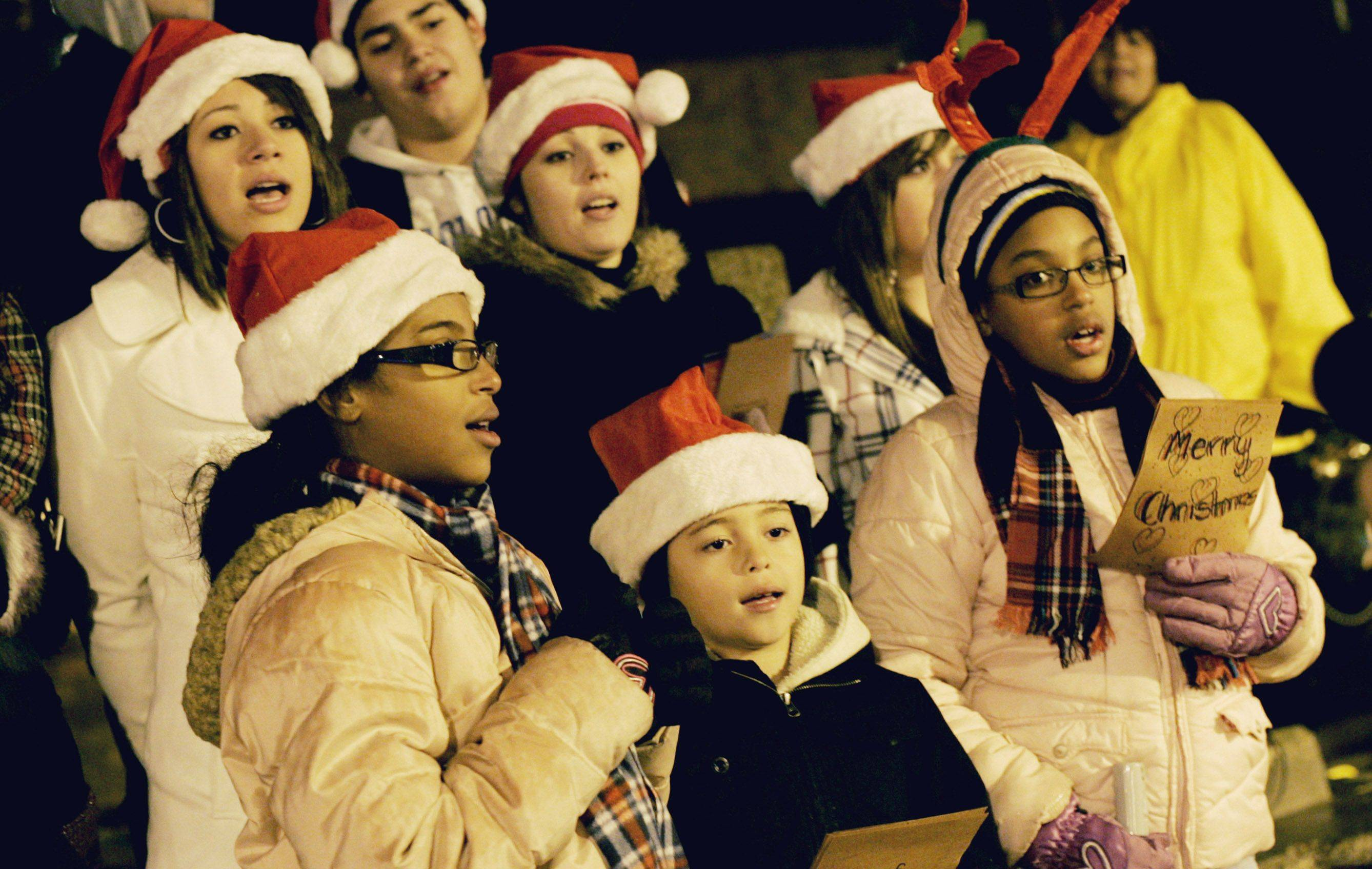 Divine Light Choir church members sings Christmas music during Aurora lights its Christmas tree Wednesday night at North Island Center in downtown Aurora.