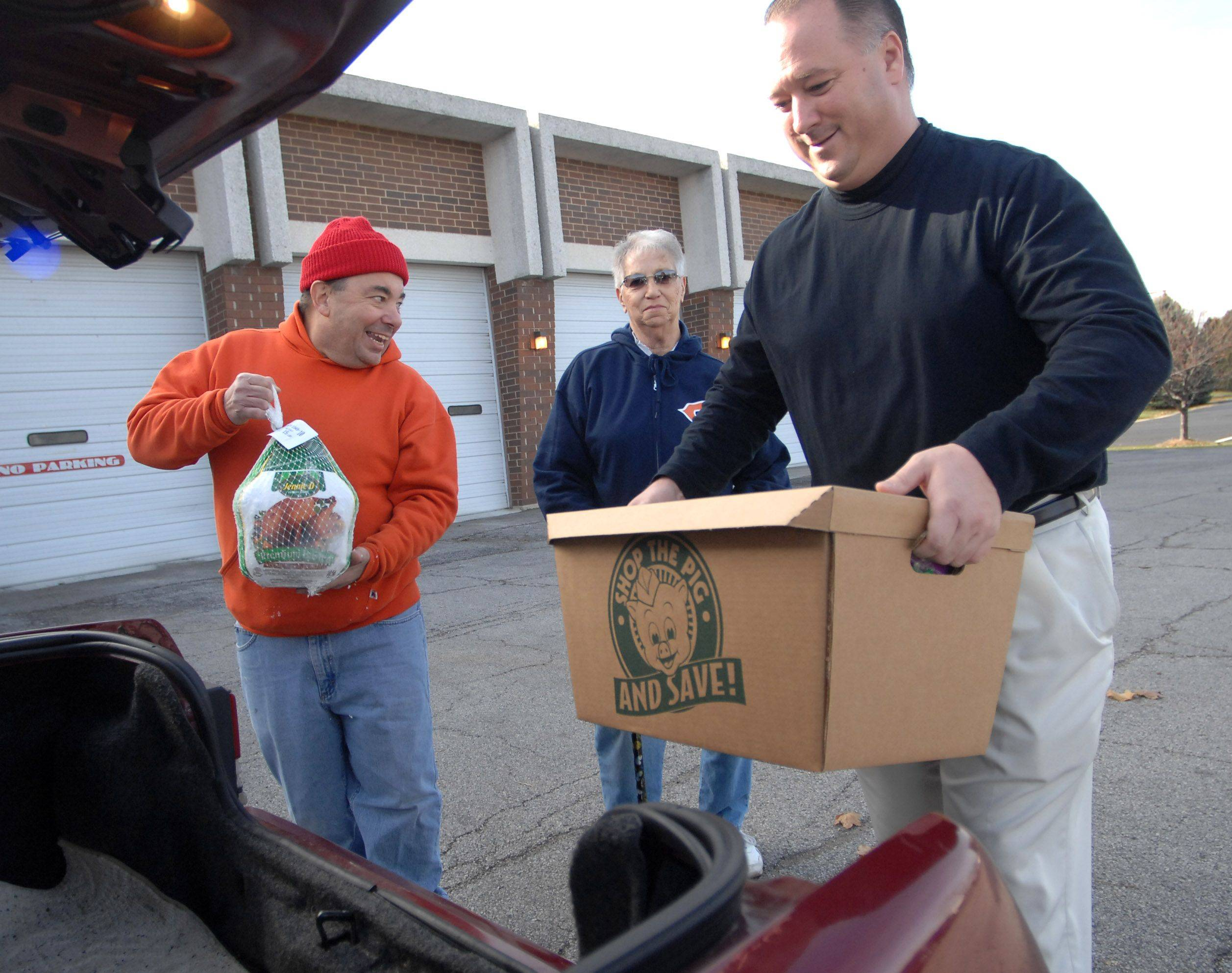 Antioch resident Dolores Matthews, center, picks up a Thanksgiving meal from the Antioch Lions Club Saturday morning. Volunteer Michael Markasovic, left, and Lions Club member Tom Sweetwood load the food into Matthews' car who was picking up the items for a relative.
