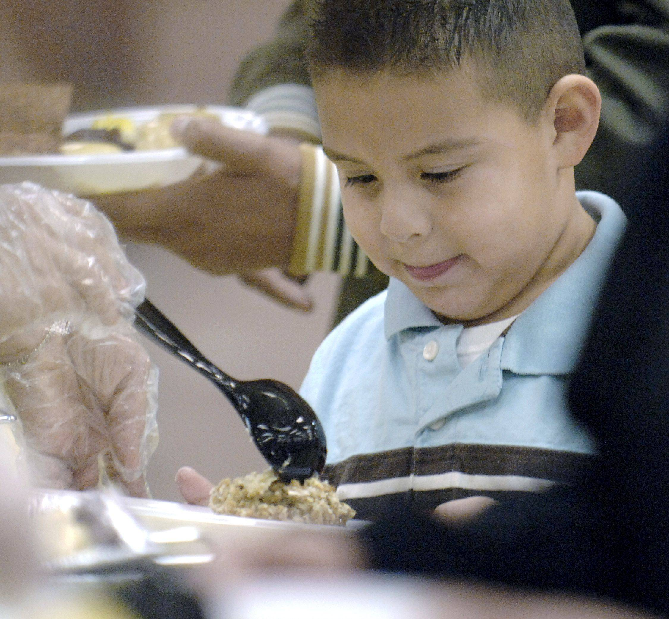 David Naranjo, 5, of Elgin gets a load of stuffing on his plate at the community Thanksgiving dinner at the Hemmens Cultural Center in Elgin on Thanksgiving Day. He preferred the side dishes and skipped the turkey.
