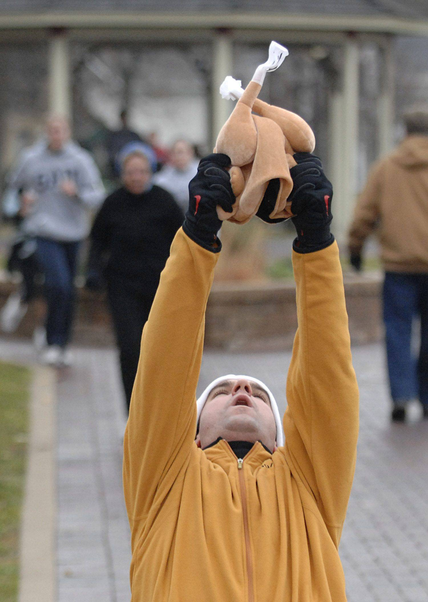 Phillip Kondos of Elgin falls to his knees and hoists his turkey hat into the air at the finish line of the Thanks A Lot! Turkey Trot 5K Fun Run and Walk in the Gifford Park neighborhood in Elgin on Thanksgiving Day. Kondos, his wife, Chelsea, and her family all took part in the event before heading back to their house for Thanksgiving dinner.