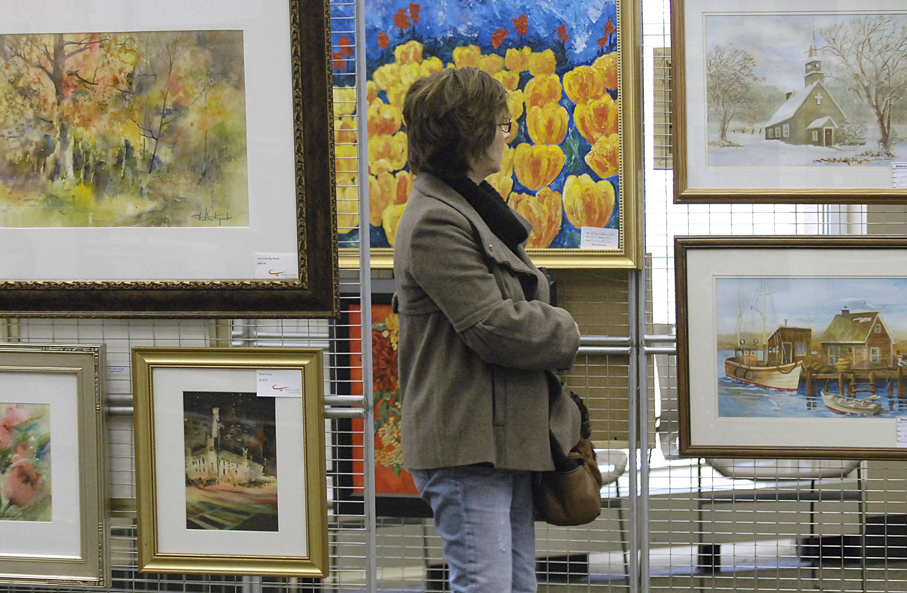 Trina Glass of North Aurora browses works by 20 Batavia Artists' Guild members on display at the Batavia Public Library on Saturday, November 20. The exhibition, which continues through Sunday from 12-4, features works of all different mediums.