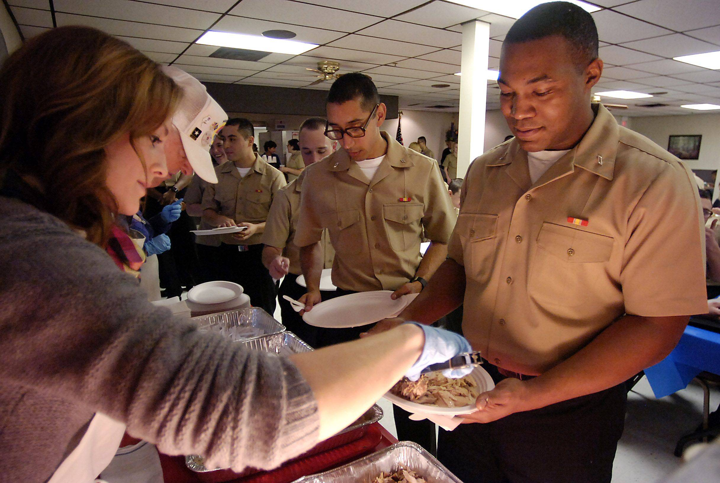 Volunteer Kristina Soukup of Arlington Heights serves up a hot turkey meal to Kyron Malone, 23, of Tennessee, just one of nearly 100 Great Lakes recruits that spent their Thankgiving Day holiday at the Amvets Post 66 in Wheeling.