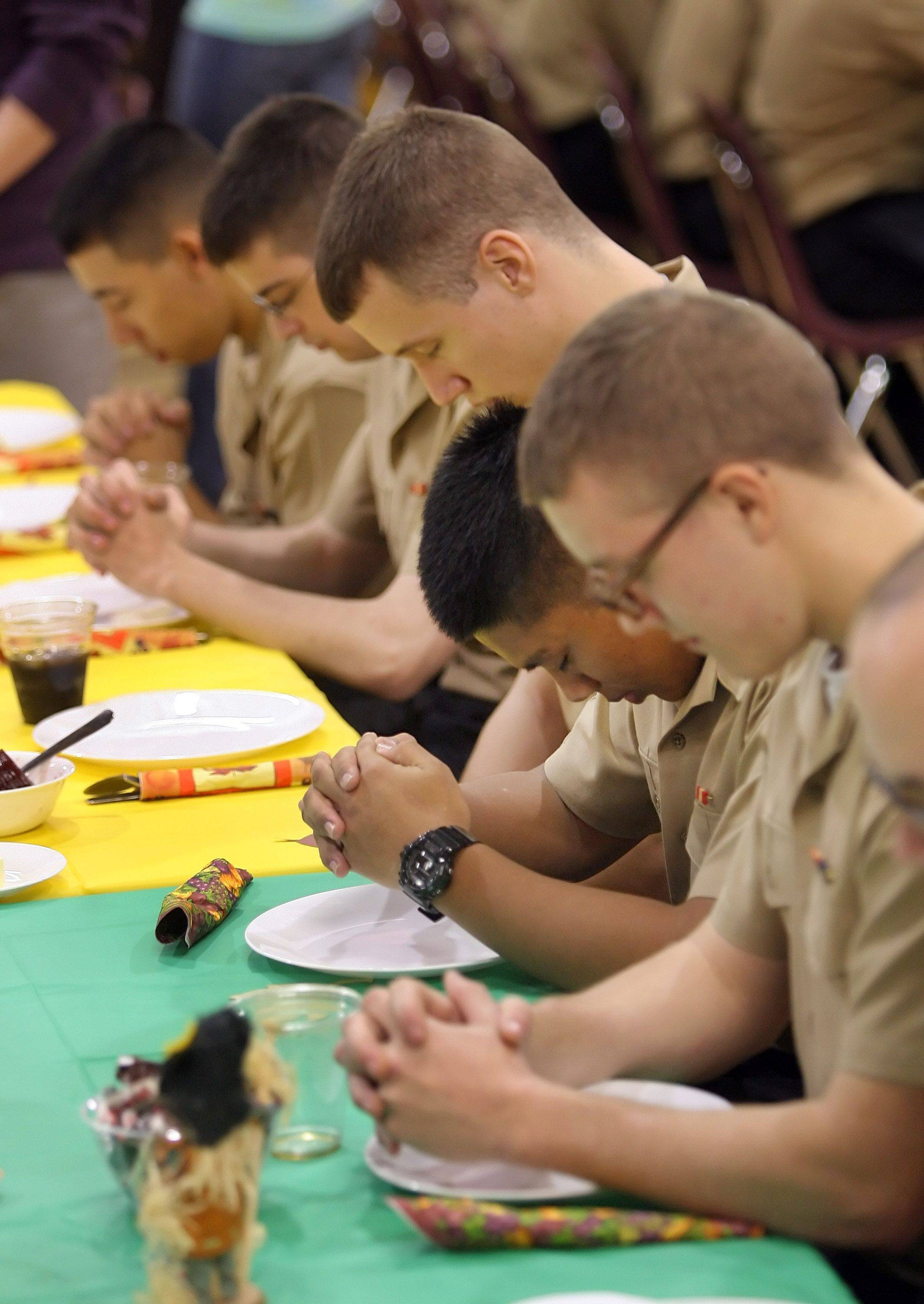 Sailors bow their heads during grace as Gurnee Community Church hosted 193 sailors from Recruit Training Command, Great Lakes for Thanksgiving dinner Thursday afternoon in Gurnee.