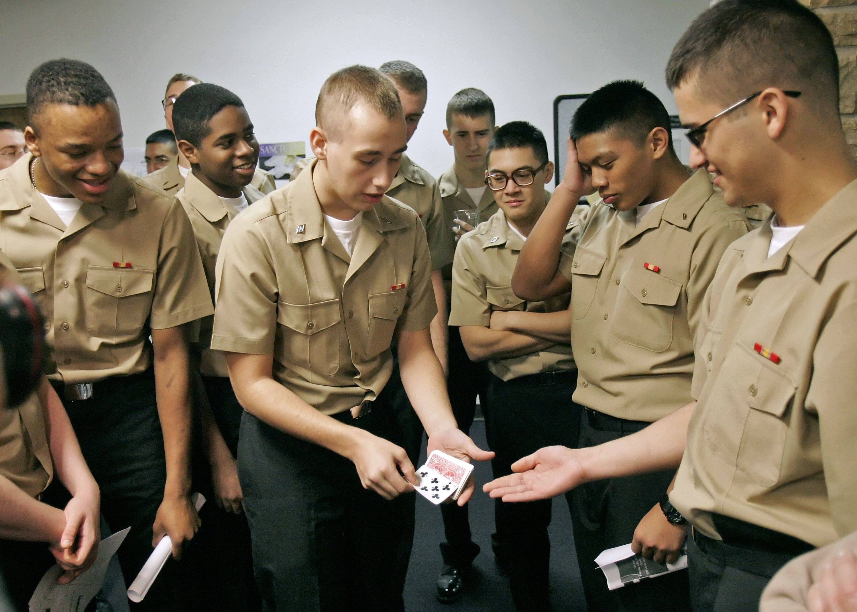Matt Higgins of Pittsburg, Pennsylvania does some magic tricks for fellow recruits as the Gurnee Community Church hosted 193 sailors from Recruit Training Command, Great Lakes for Thankgiving dinner Thursday afternoon in Gurnee.