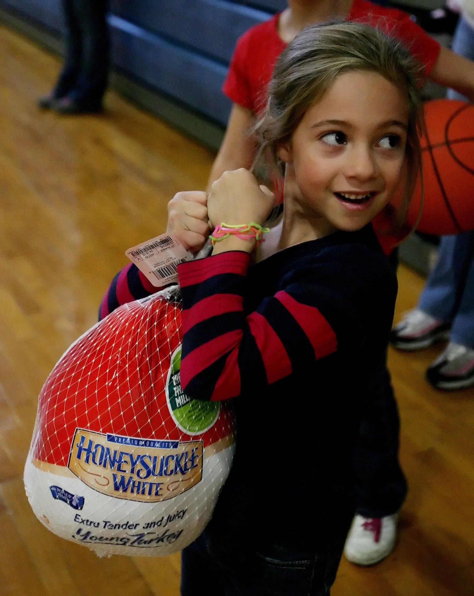 Jasmine Seiwert, 6, of Vernon Hills holds onto the turkey she won with her father, Mathias, as they shot basketball free throws to win during the Turkey Shoot sponsored by the Vernon Hills Park District Sunday in Vernon Hills.