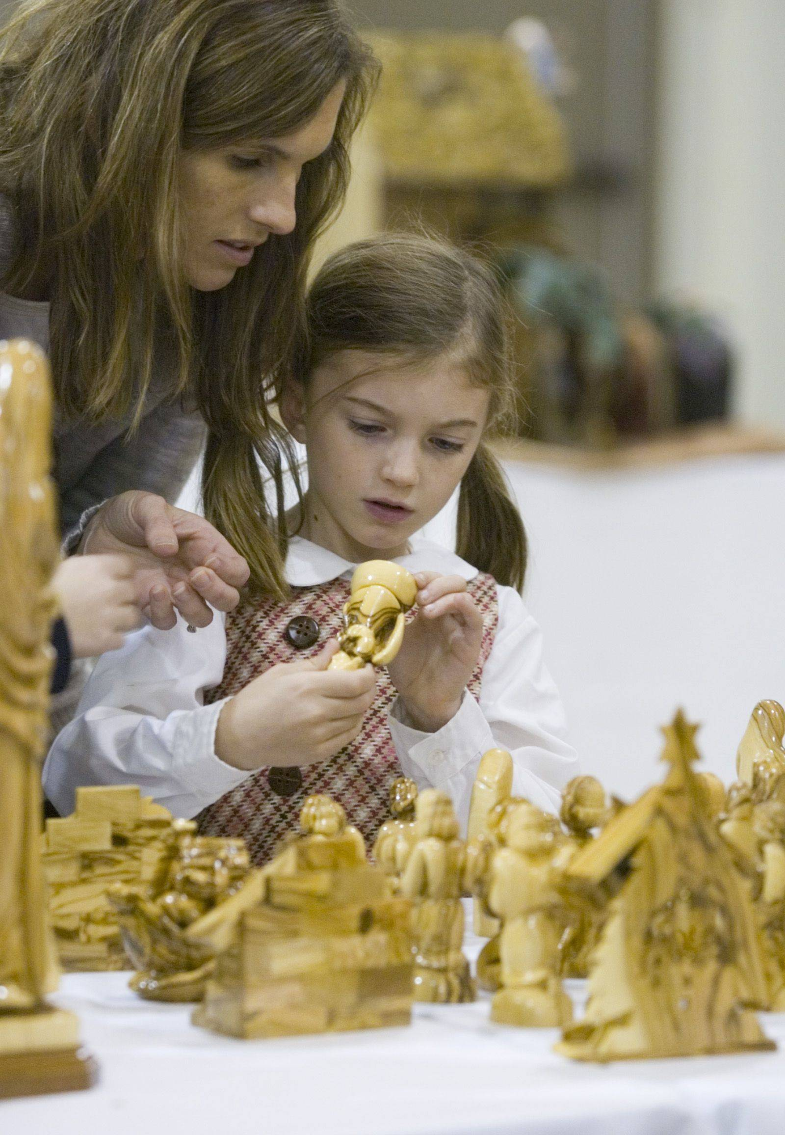 Molly Regan, age 6, and her mother, Judy Regan from Geneva, check out the handcrafted display pieces on display at St. Peter's Church in Geneva Sunday afternoon during the Nativity Exhibition.