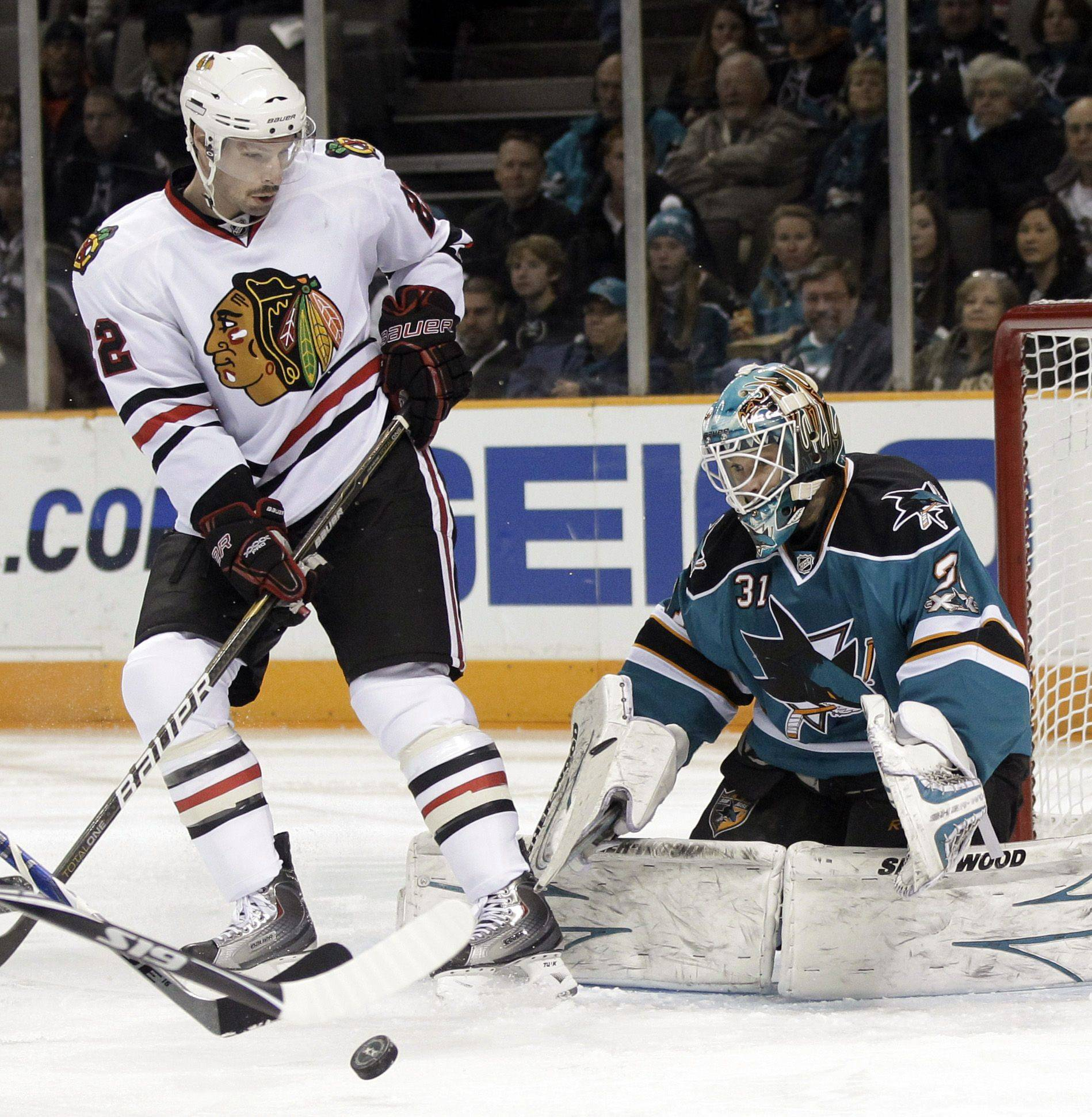 San Jose Sharks goalie Antti Niemi, right, of Finland, deflects a shot next to Chicago Blackhawks right wing Troy Brouwer during the first period of an NHL hockey game in San Jose, Calif., Wednesday, Nov. 24, 2010.