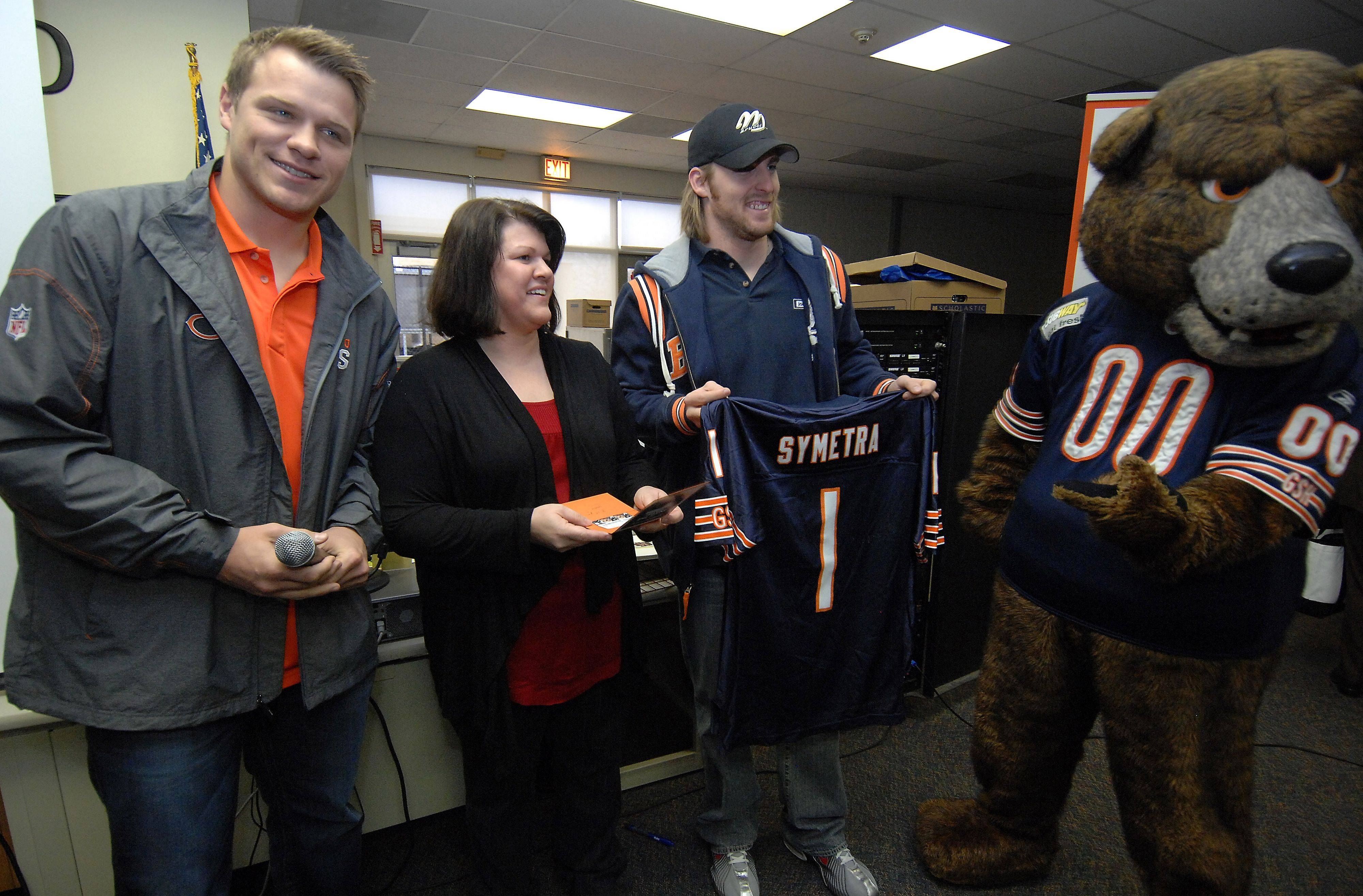 "Jennifer Ritchie, an eighth grade teacher at Mount Prospect's River Trails Middle School, received a personalized Chicago Bears jersey Tuesday from players Craig Steltz and Caleb Hanie as she was named a ""Hero in the Classroom."""