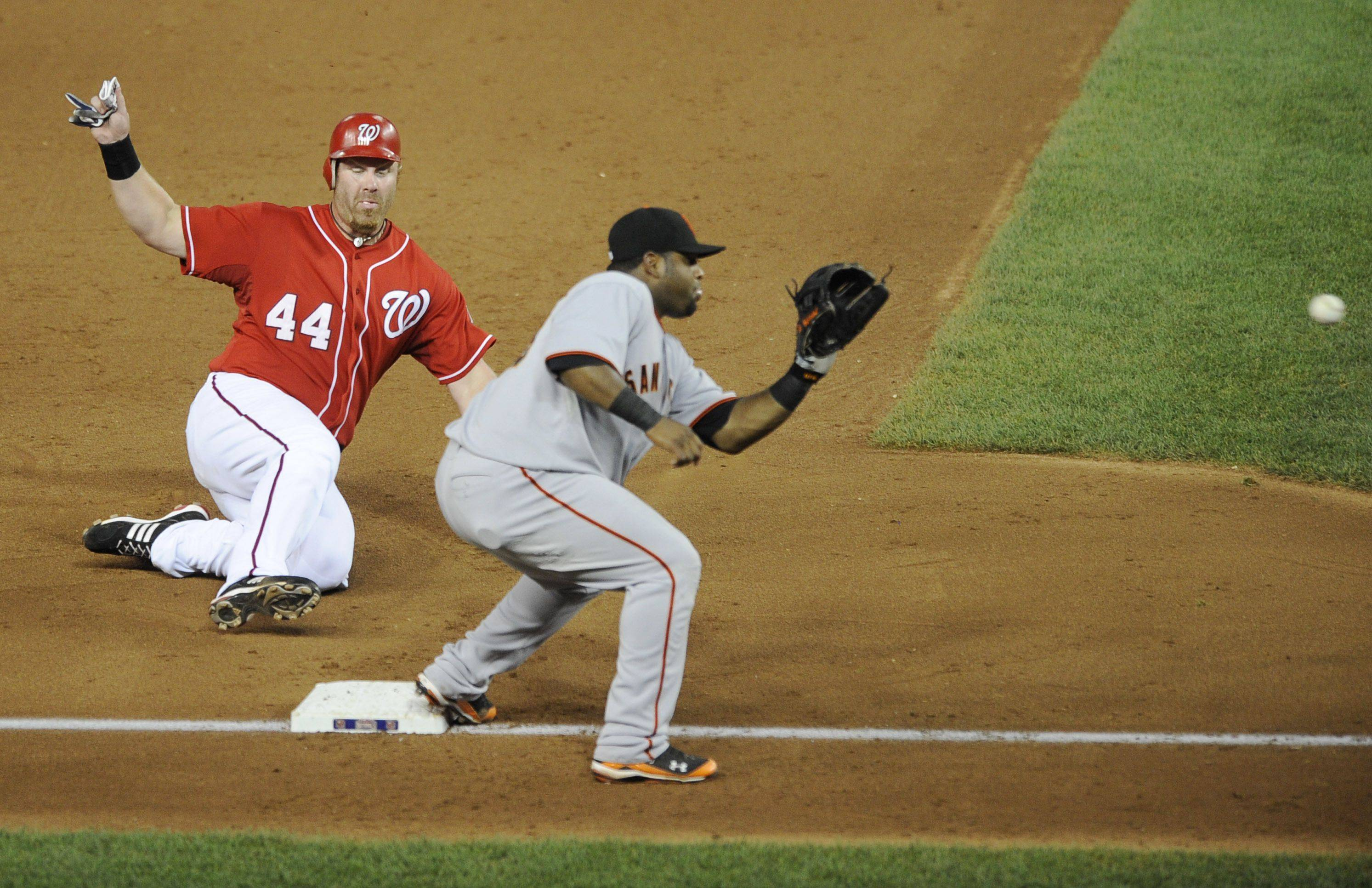 Washington Nationals first baseman Adam Dunn (44) slides safely into third on a wild pitch as San Francisco Giants third baseman Pablo Sandoval, right, waits for the ball.