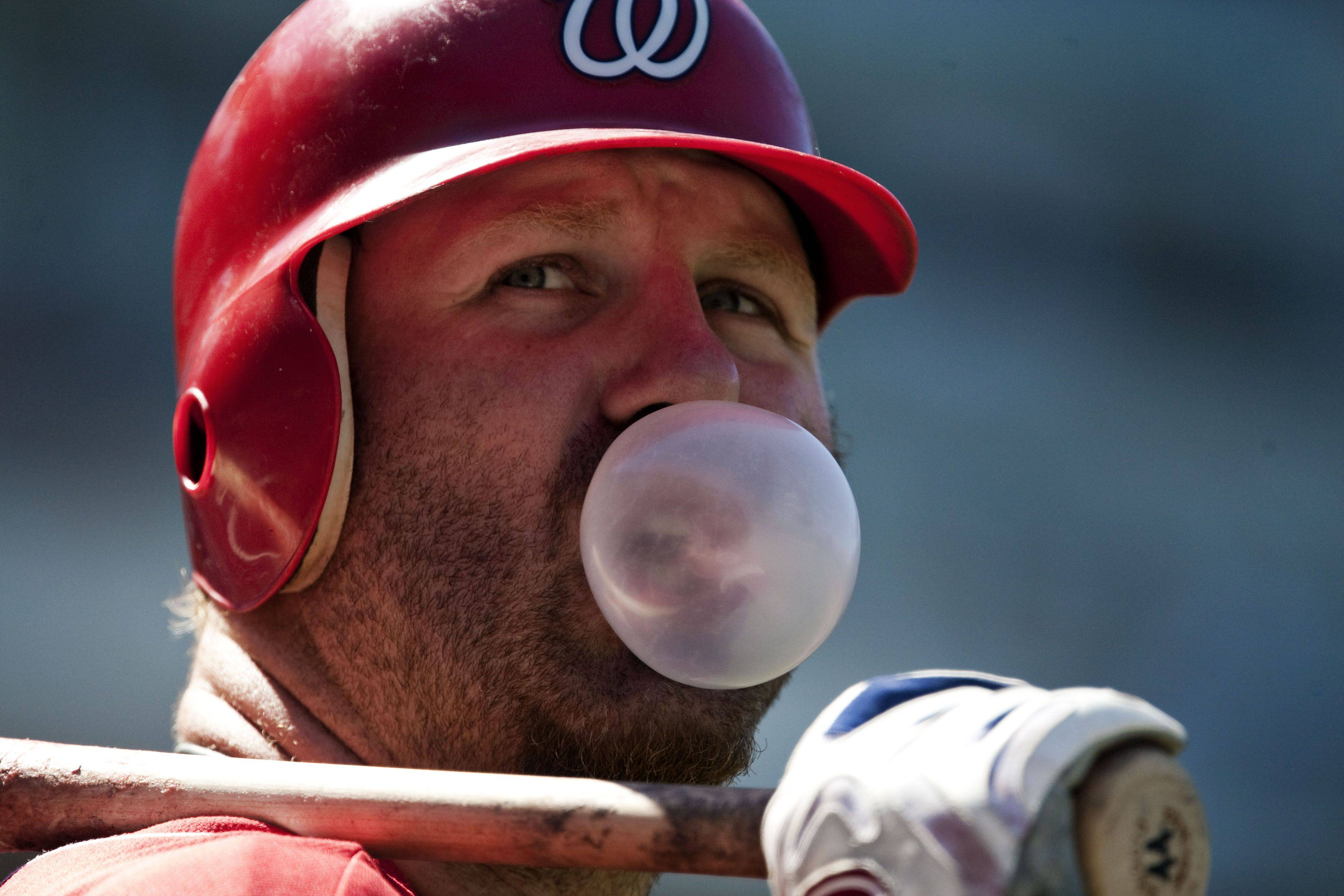 Washington Nationals' Adam Dunn blows a bubble on the on-deck circle during the sixth inning of a baseball game against the San Francisco Giants.