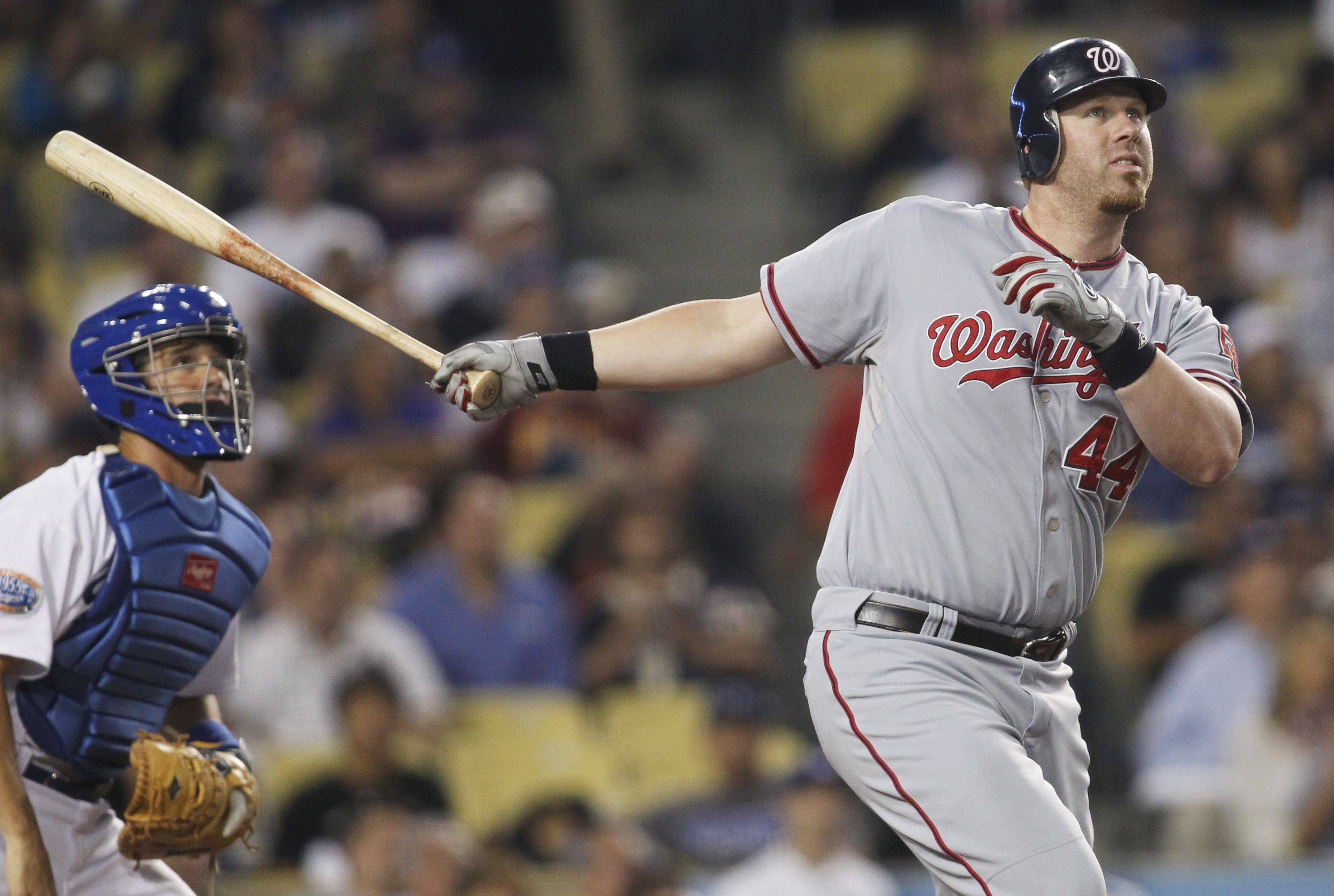 Washington Nationals' Adam Dunn, right, hits a three-run home run to also drive in teammates Ryan Zimmerman and Ian Desmond as Los Angeles Dodgers catcher Brad Ausmus, left, looks on.