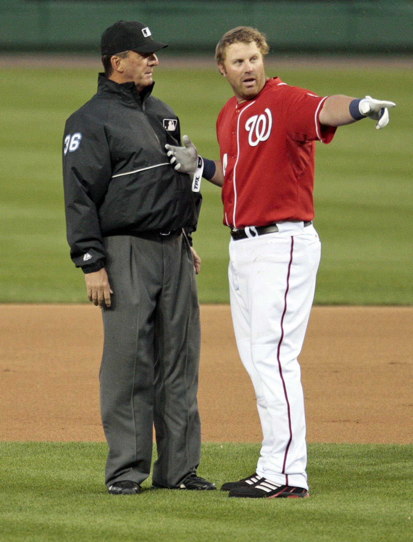Washington Nationals' Adam Dunn, right, argues with first base umpire Tim McClelland on a called strike on Friday, April 16, 2010, in Washington. Dunn was ejected.