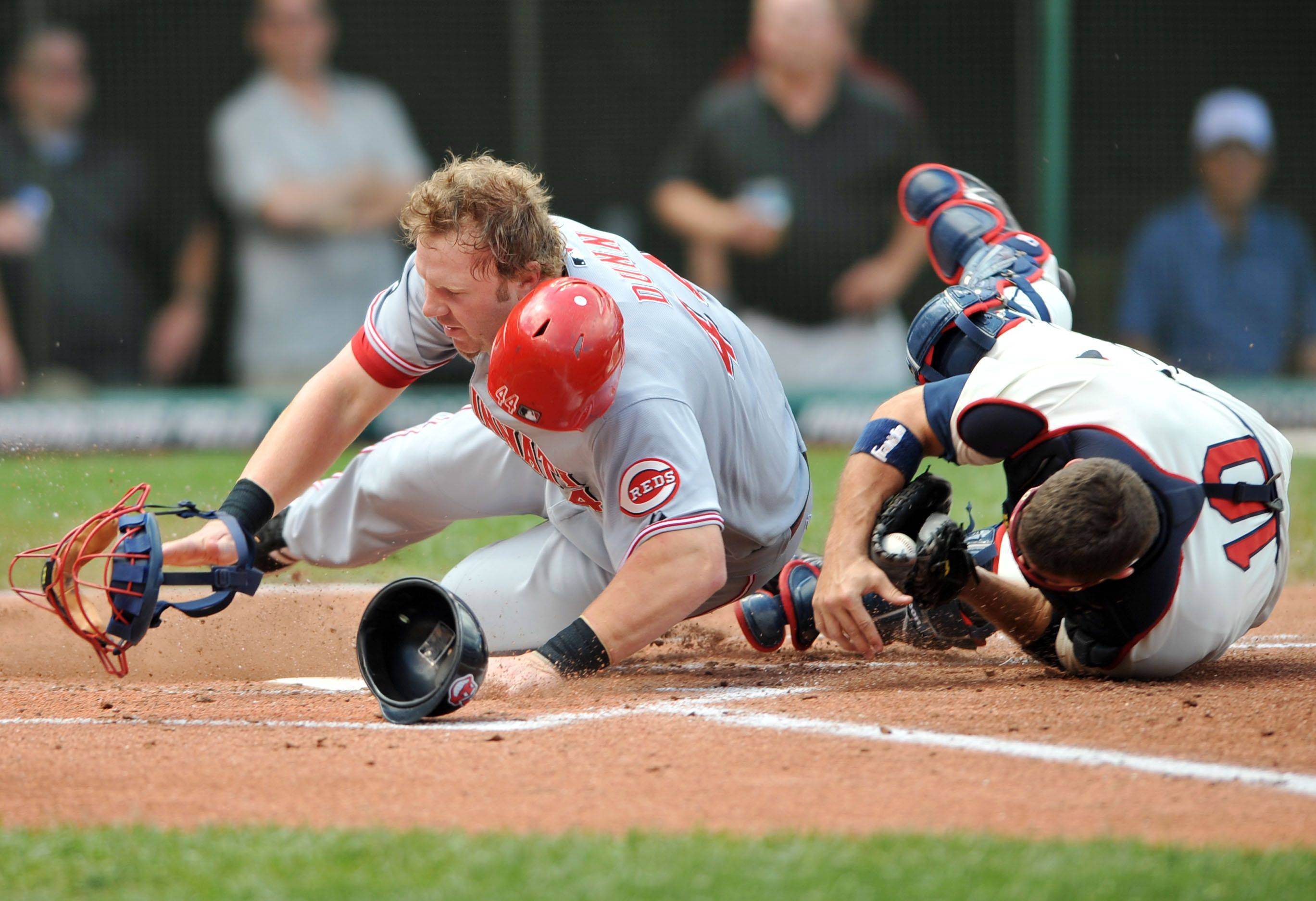 Cleveland Indians catcher Kelly Shoppach, right, holds on to the ball after tagging out Cincinnati Reds' Adam Dunn on Sunday, June 29, 2008, in Cleveland.