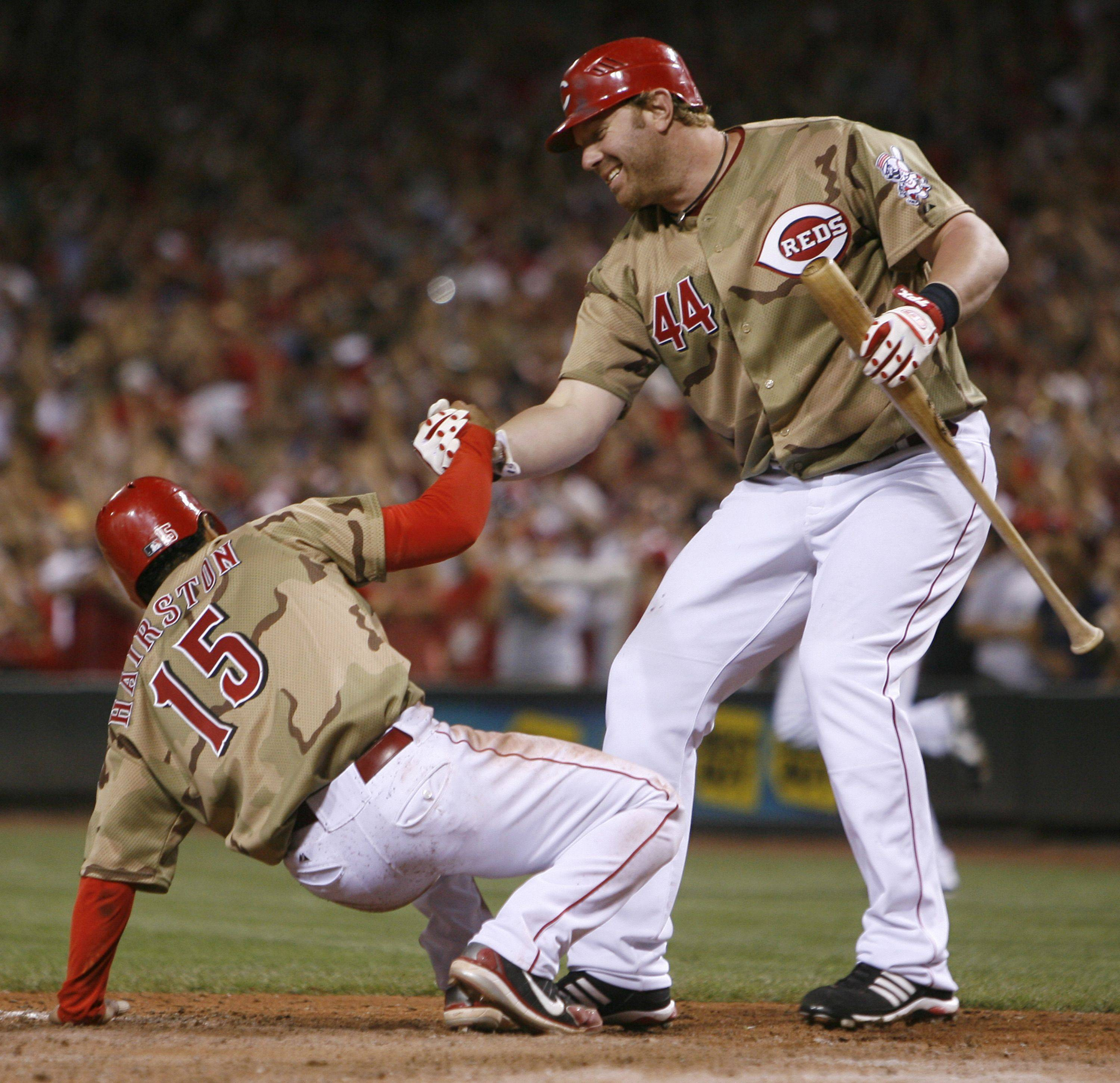 Cincinnati Reds' Jerry Hairston Jr., (15) is picked up from home plate by Adam Dunn (44) after Hairston Jr. , Saturday, July 5, 2008 in Cincinnati.