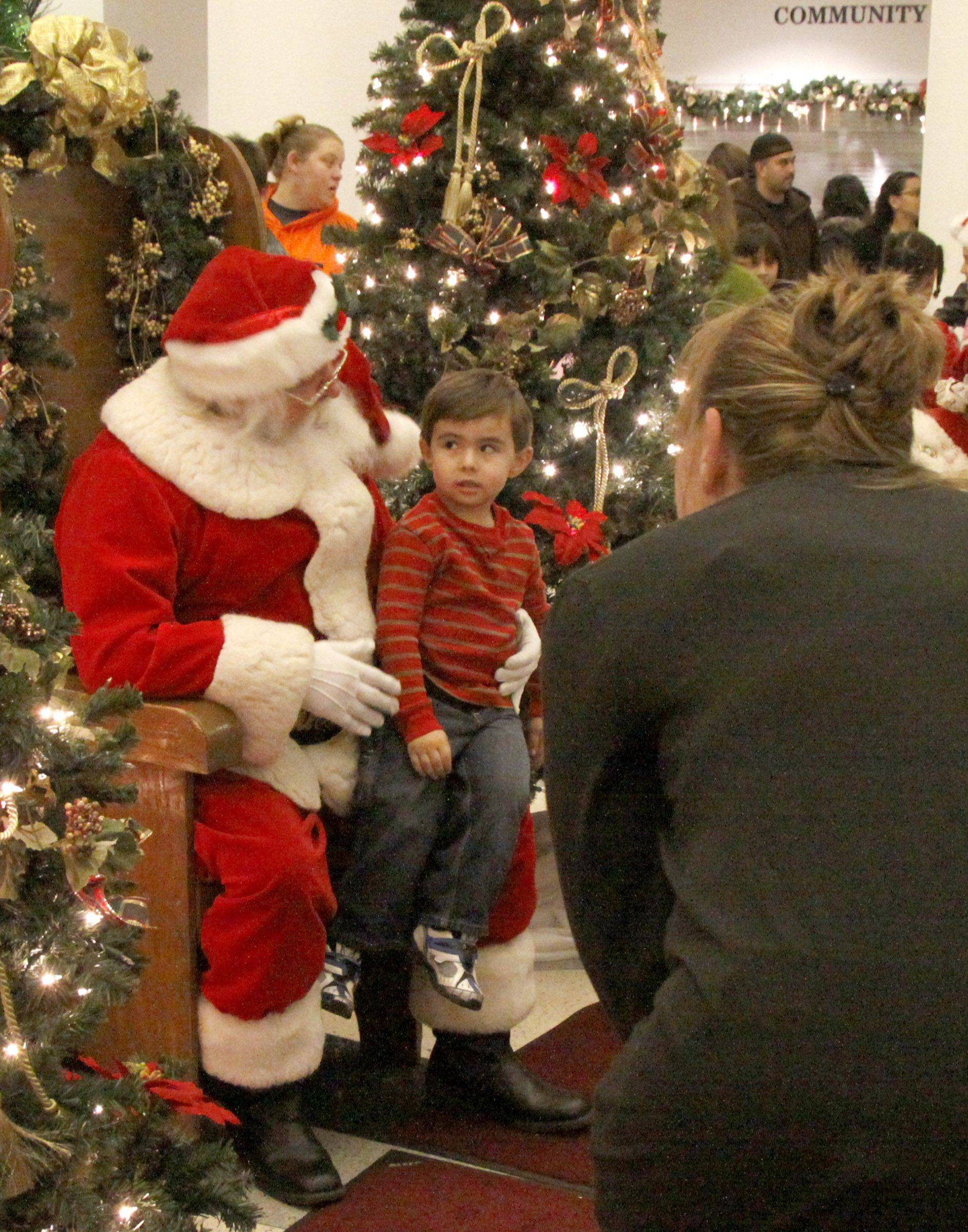 Rylan Rico, 4, of Addison sits on Santa's lap while his mother Jodi Krush tries to get him to smile for the camera. People came out to celebrate the season Friday at Addison's Village Hall. Pictures with Santa, ornament making and games were available for children of all ages.