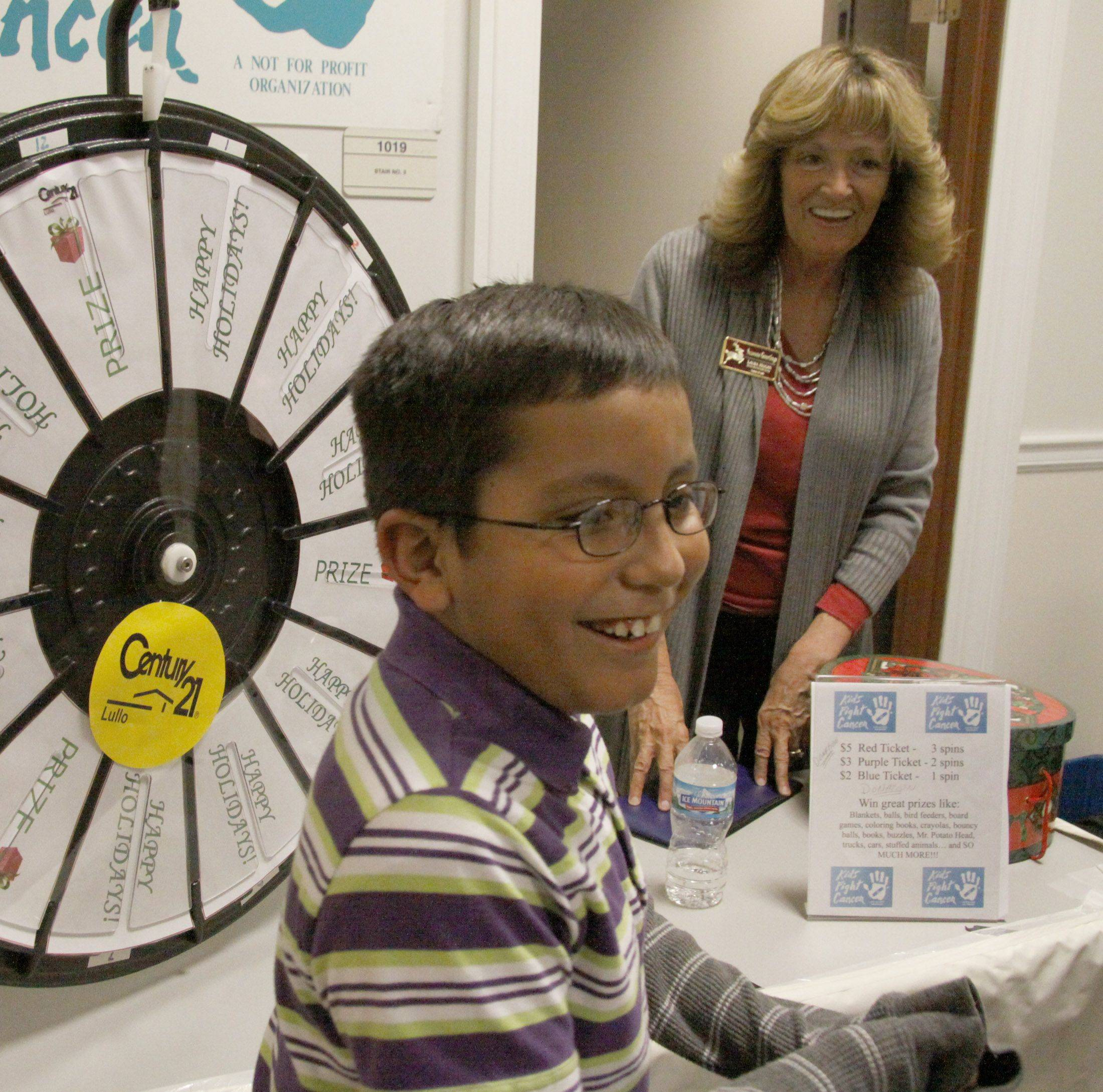 Laura Hogan looks on as Kevin Esparca, 9, of Addison reveals his excitement after he spun on the prize wheel at Friday's celebration of the season in Addison.