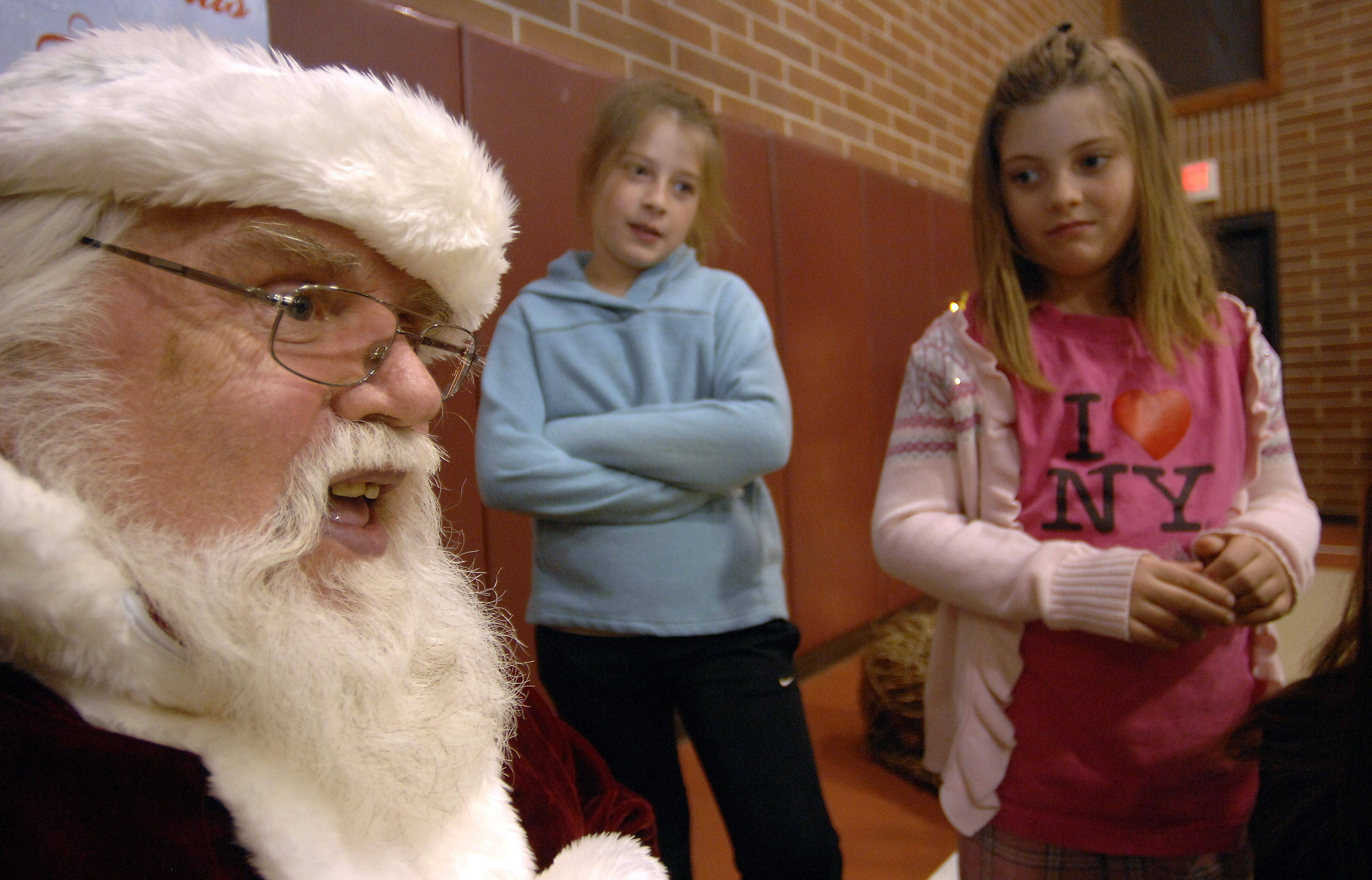 Rich Holtz of Des Plaines listens to kids' wishes. Among the kids were Annika ,9, and Katherine Knuth ,7, of Inverness who took part in the Inverness Park District's Hometown Holiday Celebration on Friday.