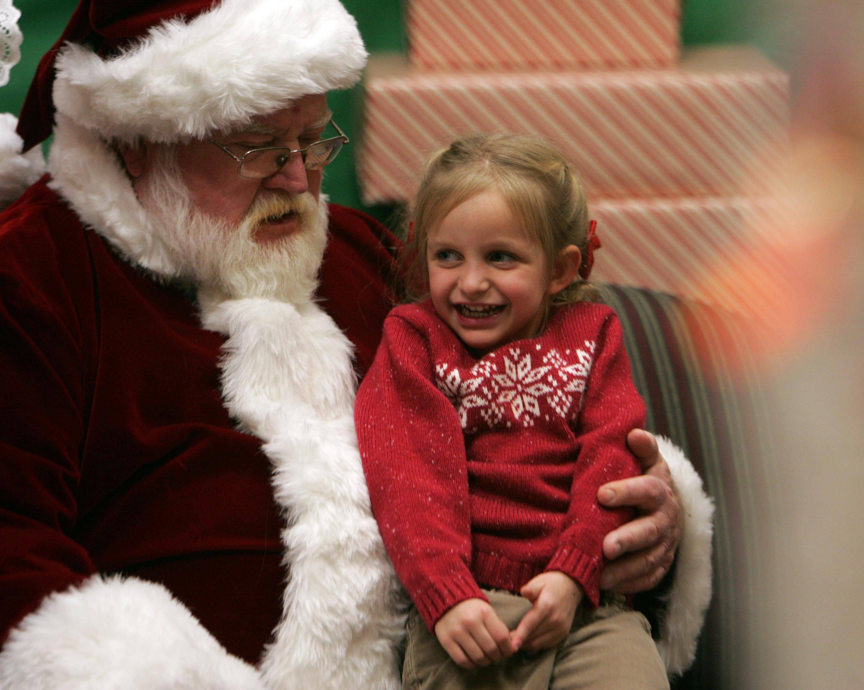Four-year-old Sophia Arnold of Burlington tells Santa her wish list as he visits the Town and Country Library in Elburn . Arnold was hoping for a new house and a new baby crib.