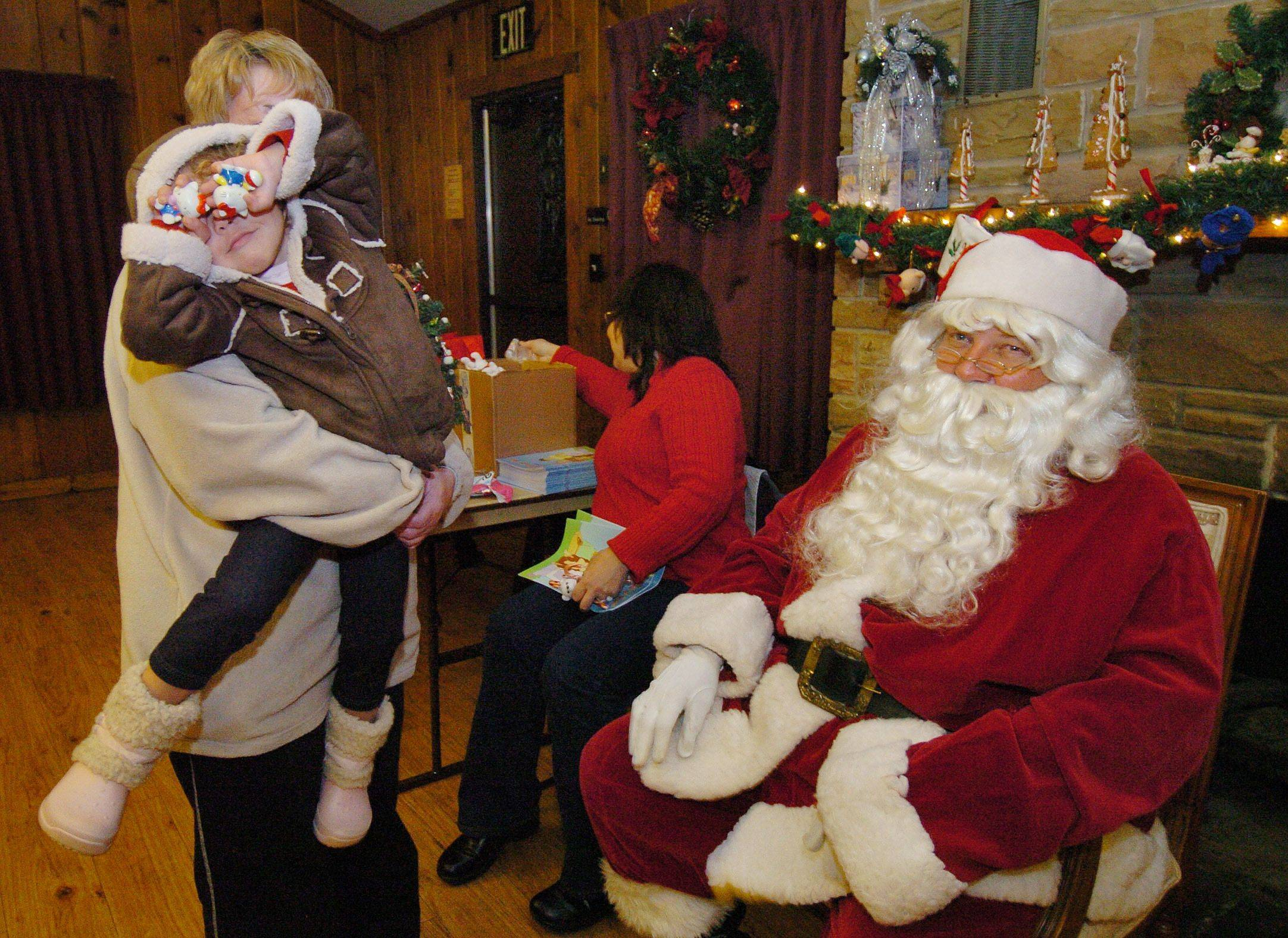 Three-year-old Janissa Bauer has a problem relating to Santa to the point of shielding her eyes, while being held by her grandmother Barbara Bauer, in the log cabin prior to Christmas tree lighting in Bartlett Park.