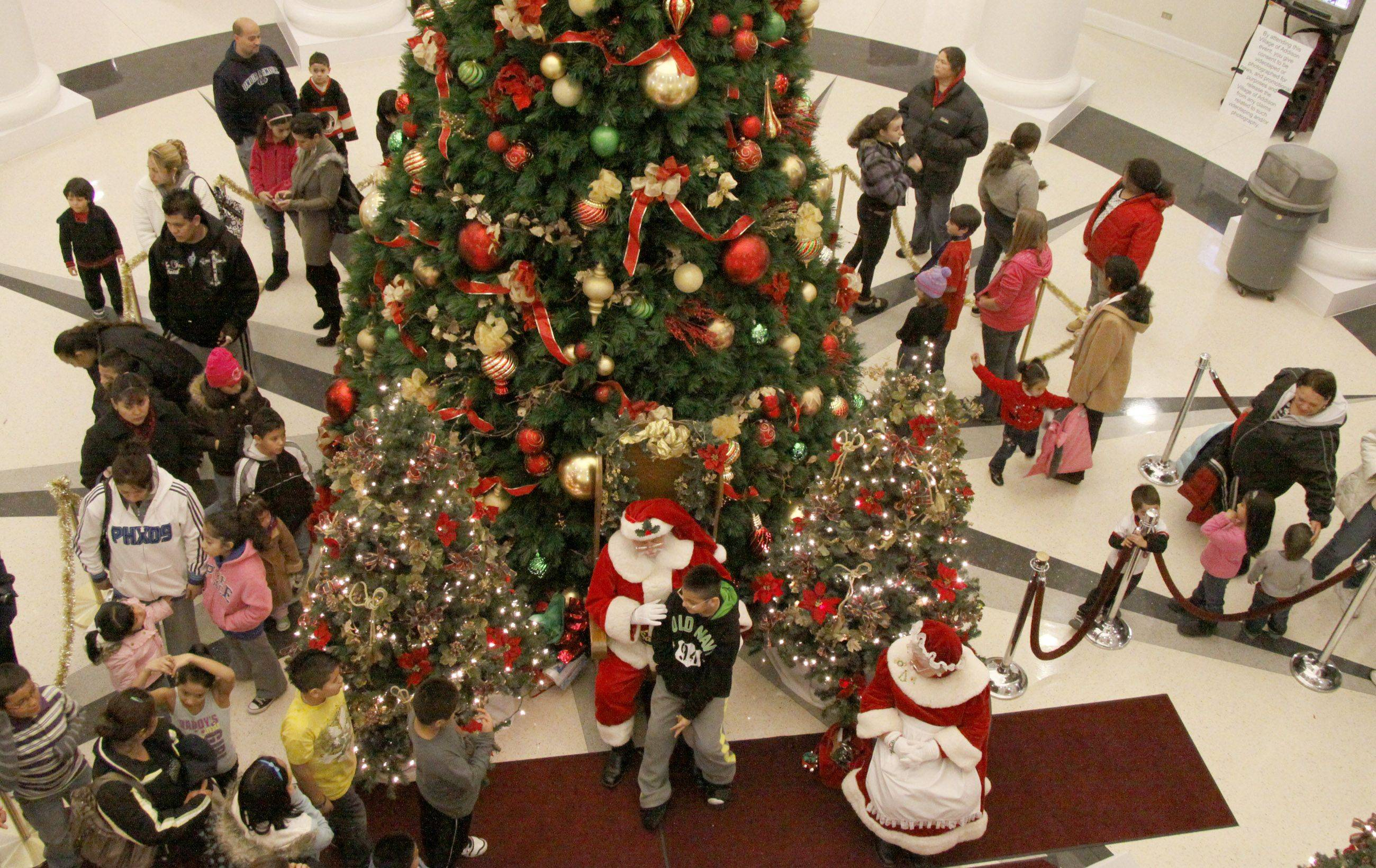 People wait in line around the Christmas Tree to have their picture taken with Santa Friday at Addison's Village Hall.