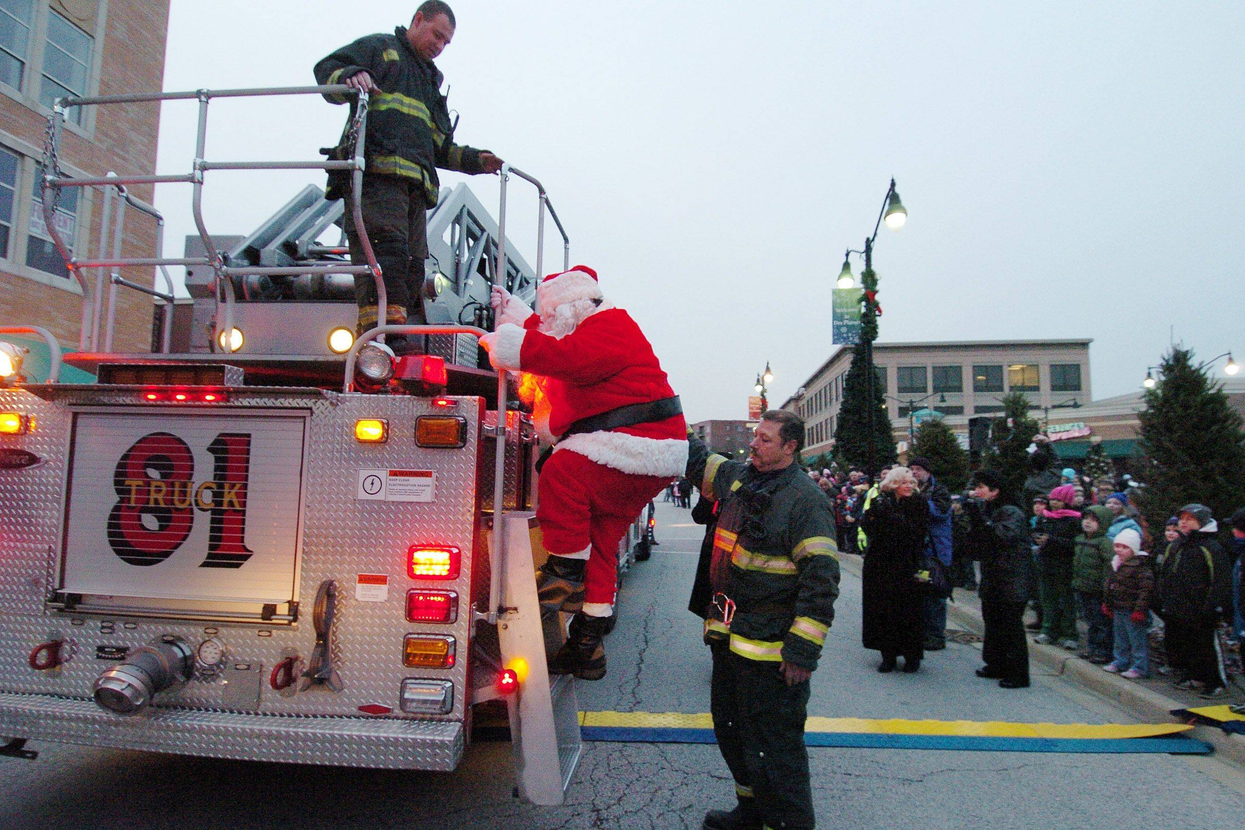 Santa is helped down from a fire truck by Des Plaines firefighters as he arrives for the Des Plaines Christmas tree lighting street fest at Metropolitan Square.