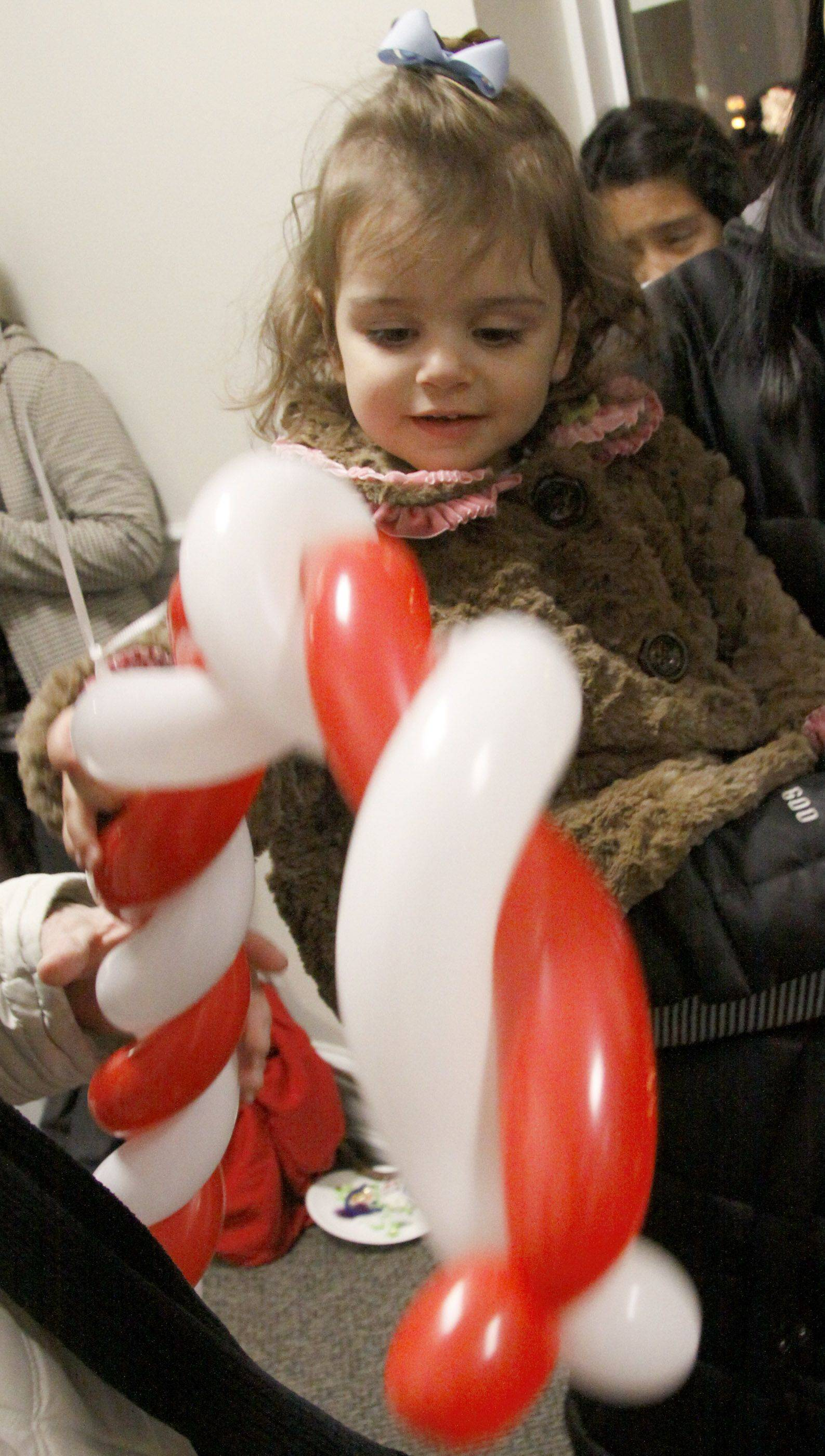 Anna Natalizio, 1, of Bloomingdale holds her candy cane balloon at Addison Village Hall's celebration of the season. Pictures with Santa, ornament making and games were available for children of all ages.