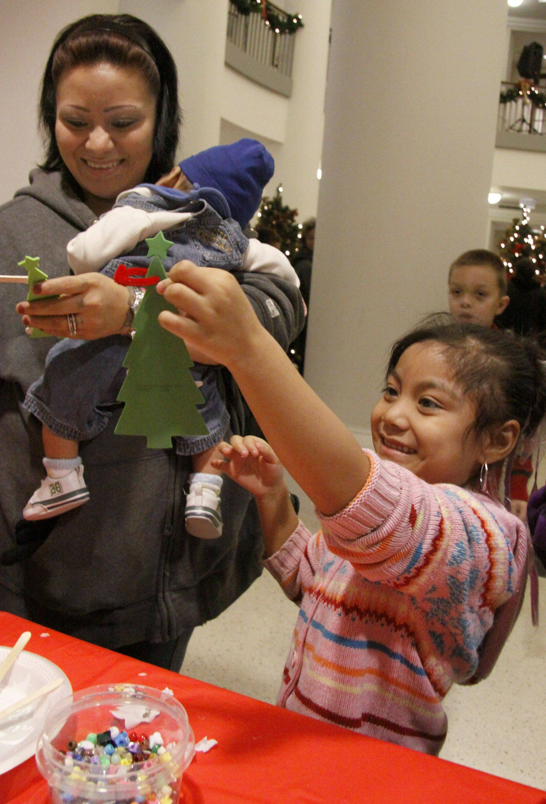 Jessica Sanchez, 5, of Addison shows her ornament to her mother Maria Friday in Addison.