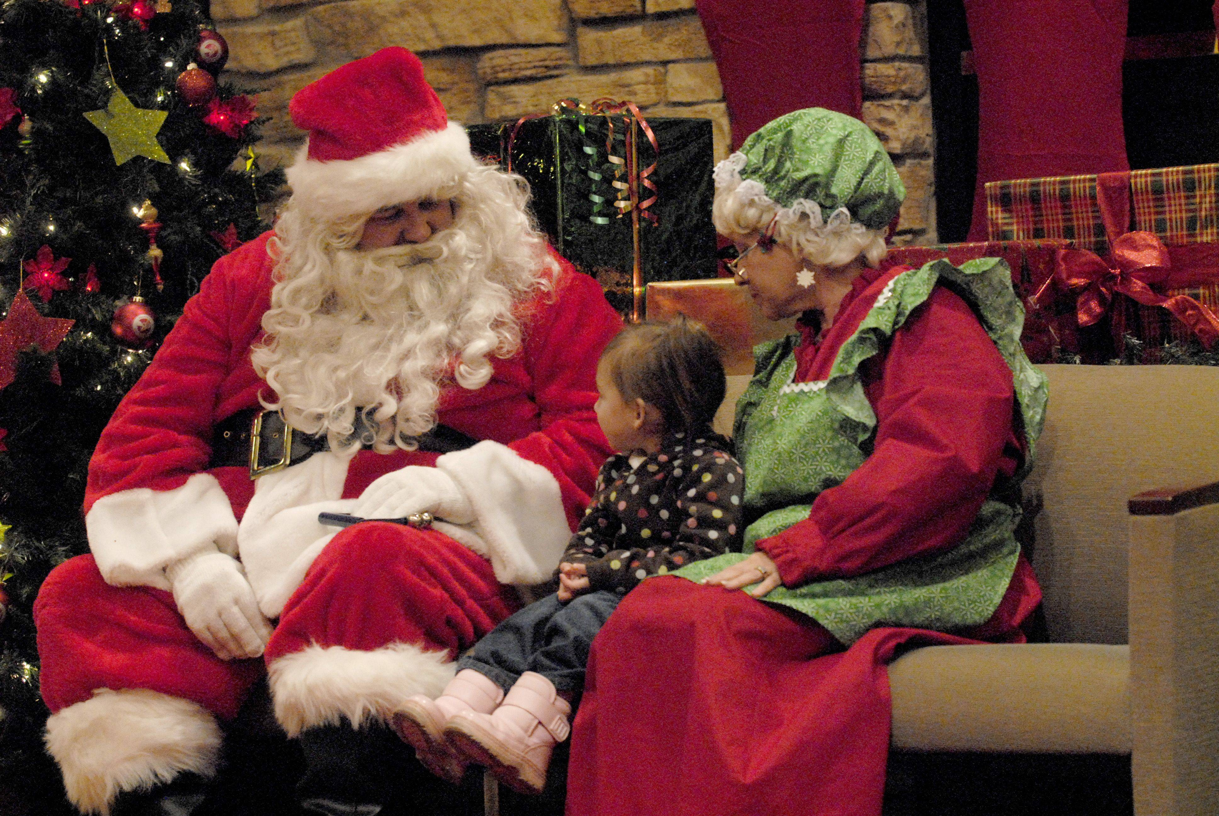 Ava Ramirez, 3, from Lake in the Hills explains to Santa and Mrs. Claus what she would like for Christmas during the Festival of Trees gathering Friday night at the Village Hall in Lake in the Hills.
