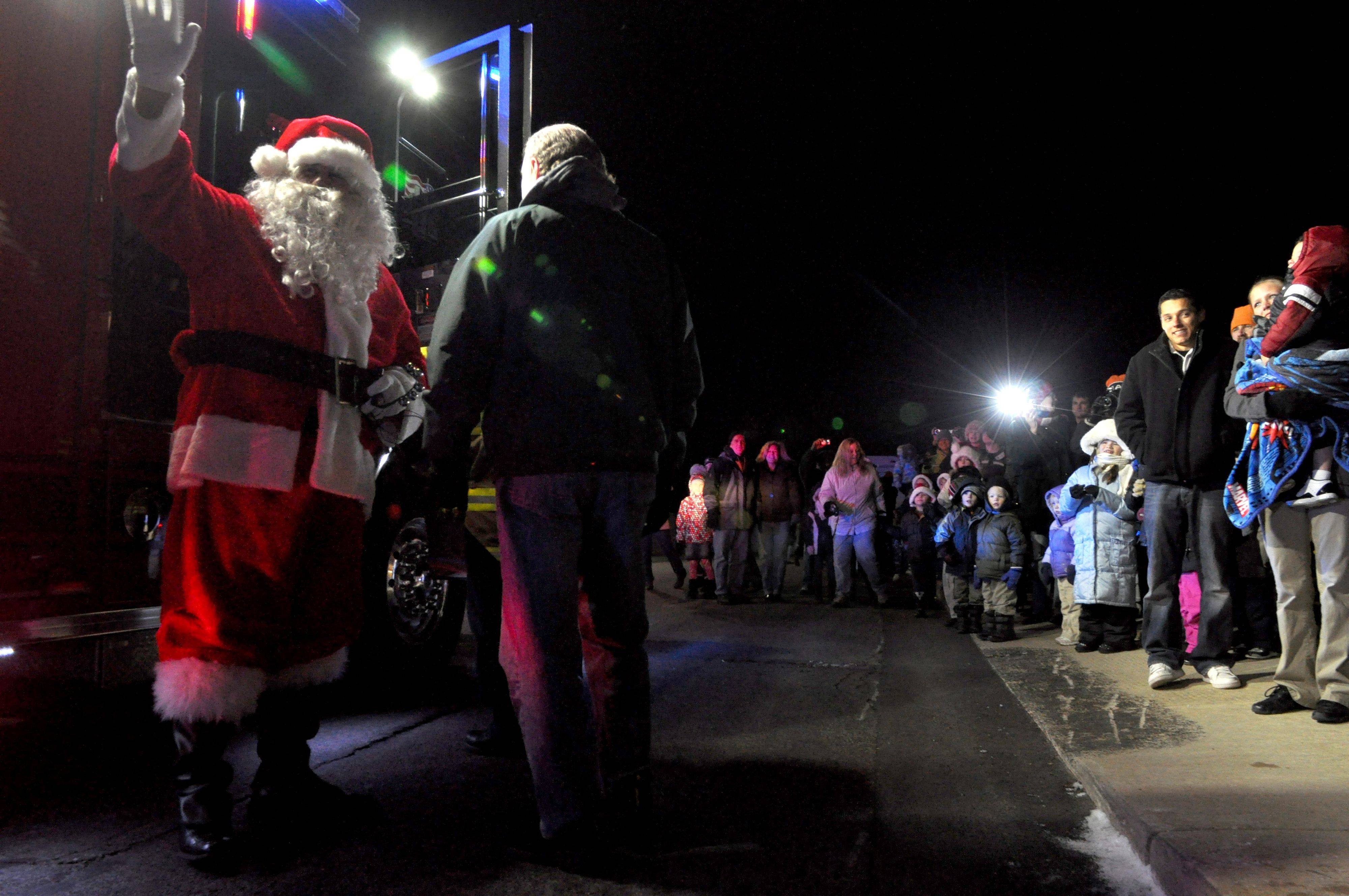 Village President Ed Plaza escorts Santa and Mrs. Claus as they arrive via fire truck at the Festival of Trees gathering Friday night at the Village Hall in Lake in the Hills.