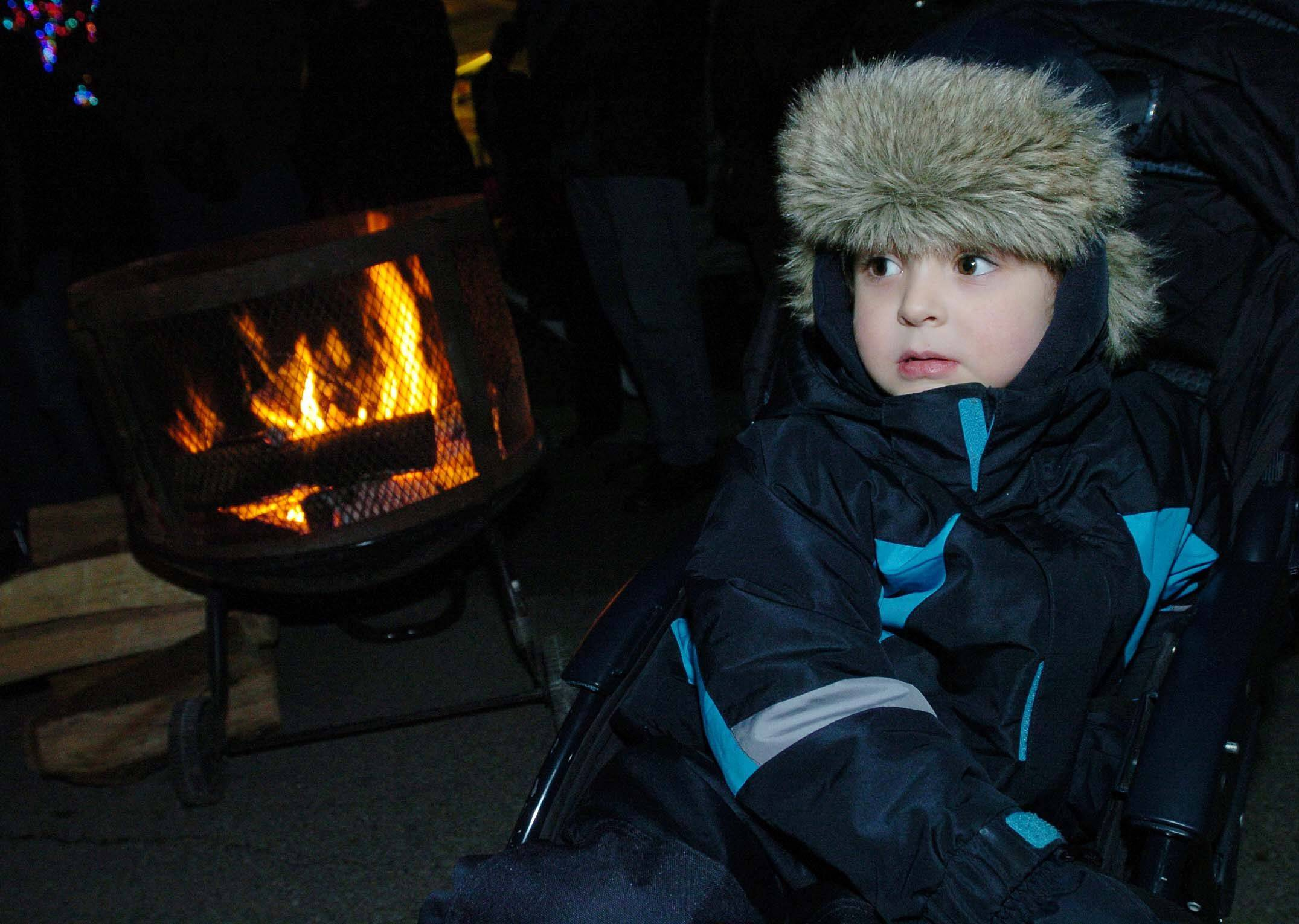 John Ogan,4, of Warrenville keeps warm by the fire while waiting for Santa to show during Holly Days in Warrenville Friday.