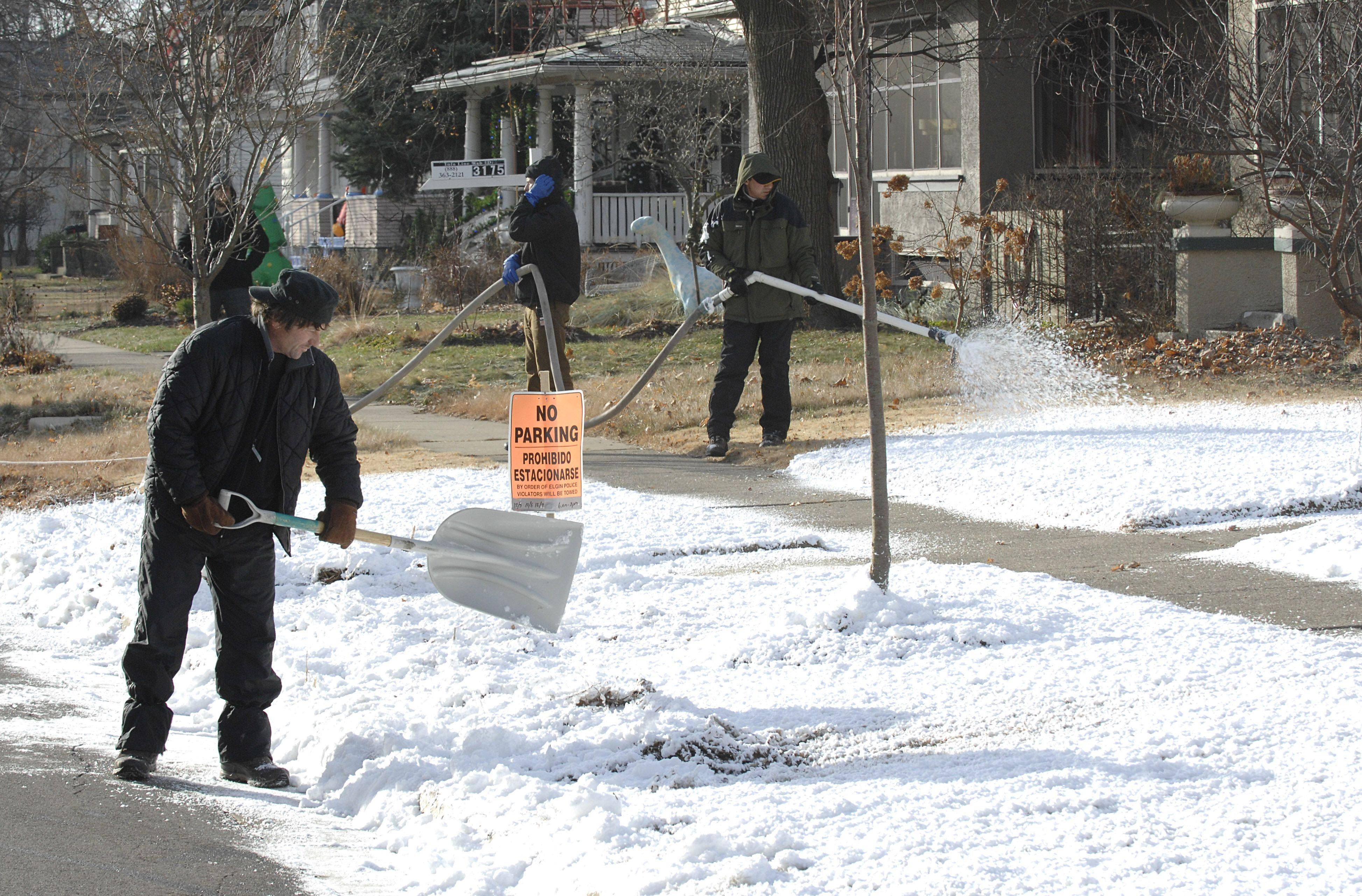 "Jeffrey Hurt shovels freshly made ""snow"" while Ted Corso sprays more onto the front lawns of homes across the street from the emergency bay of the old Sherman Hospital on Spring Street in Elgin for the movie, ""Contagion."""