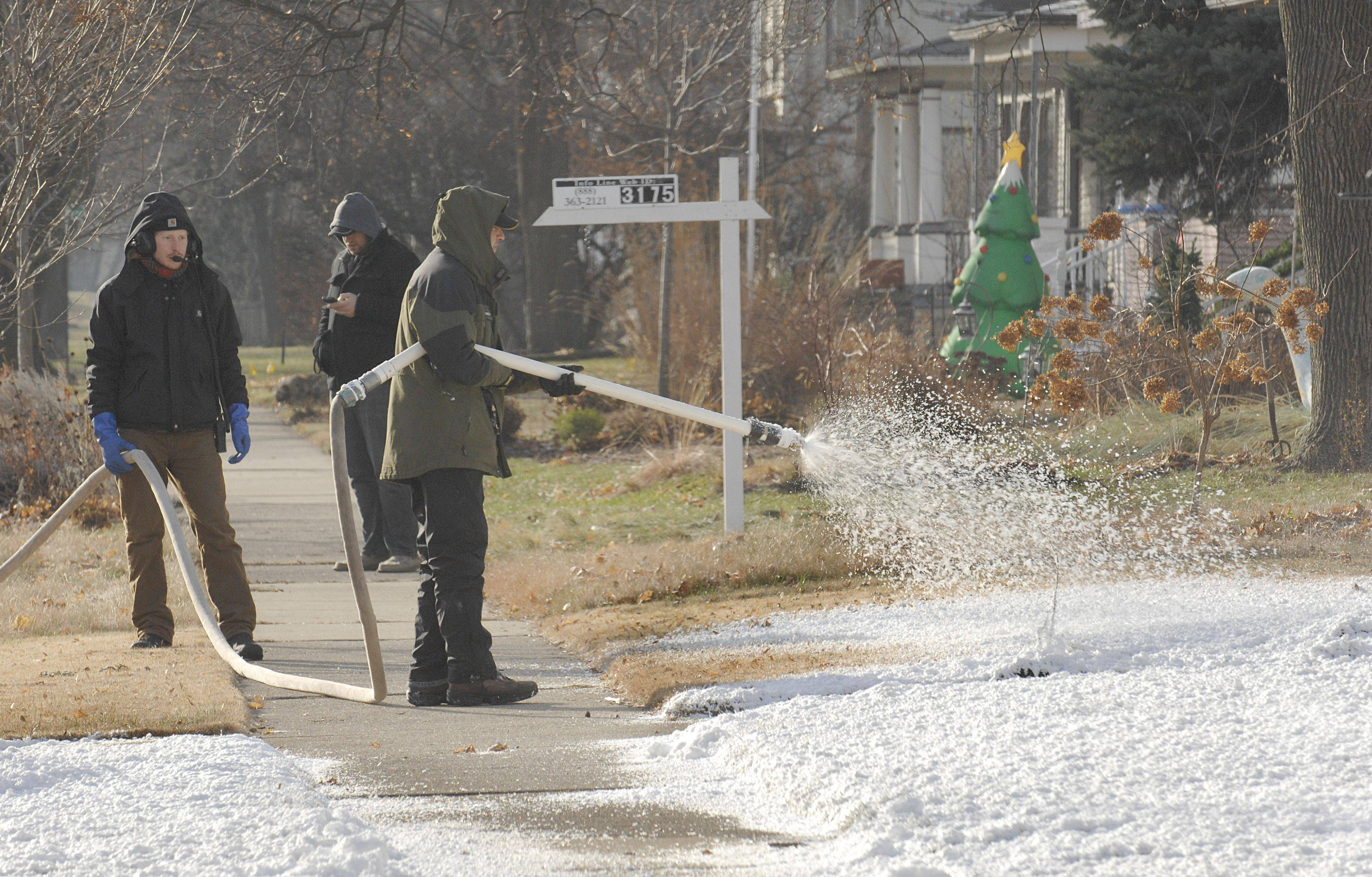 "Ted Corso sprays manufactured snow onto the front lawns of homes across the street from the emergency bay of the old Sherman Hospital for the movie ""Contagion."" It was comprised of foam and ice."