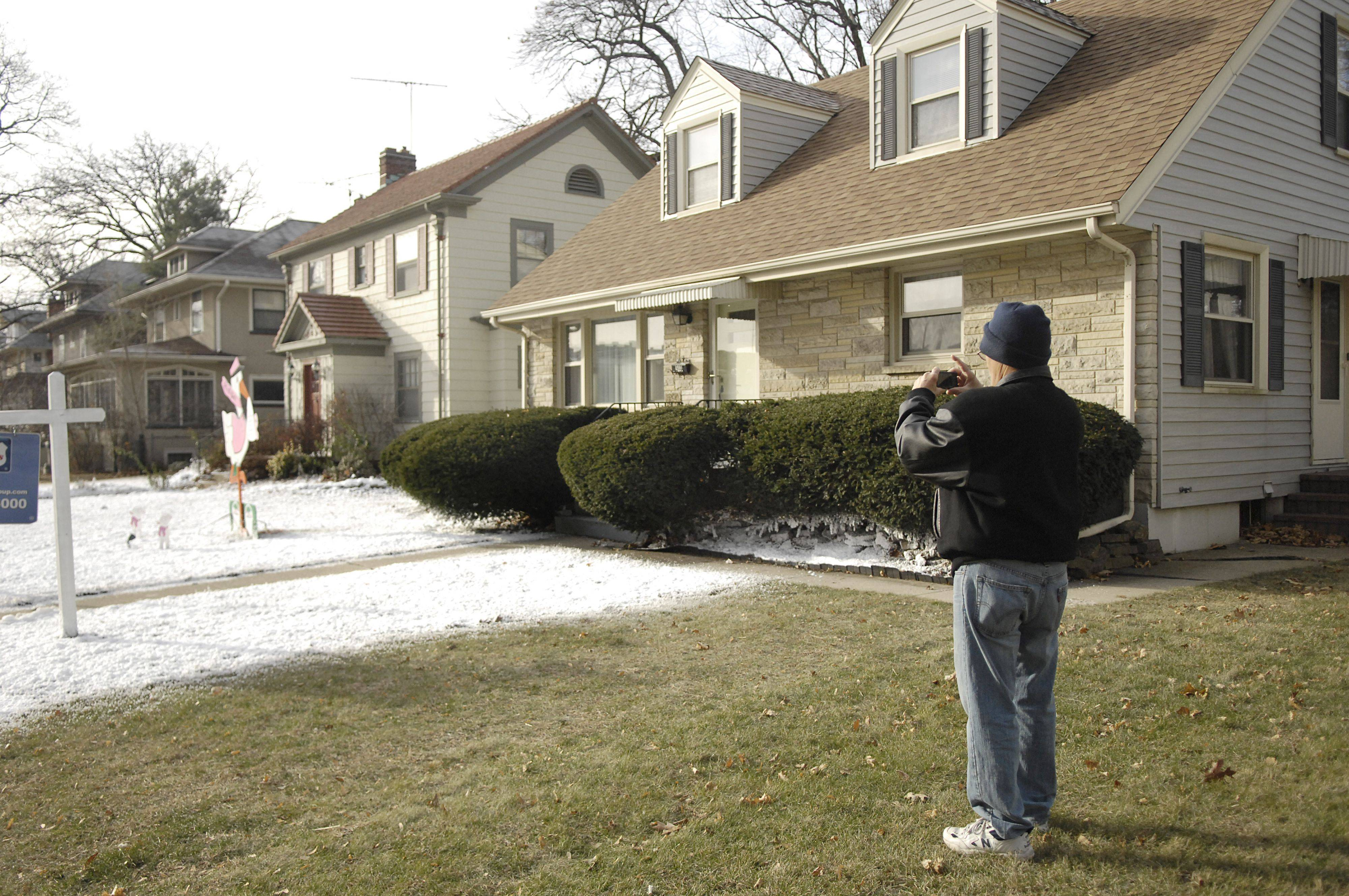 "Luis Vale takes a photo of his daughter's front lawn, one of two partly covered in fake snow. The home is across the street from the emergency bay of the old Sherman Hospital on Spring Street in Elgin. It will be in the background shot for the movie ""Contagion."" The movie studio compensated both homeowners for their trouble."