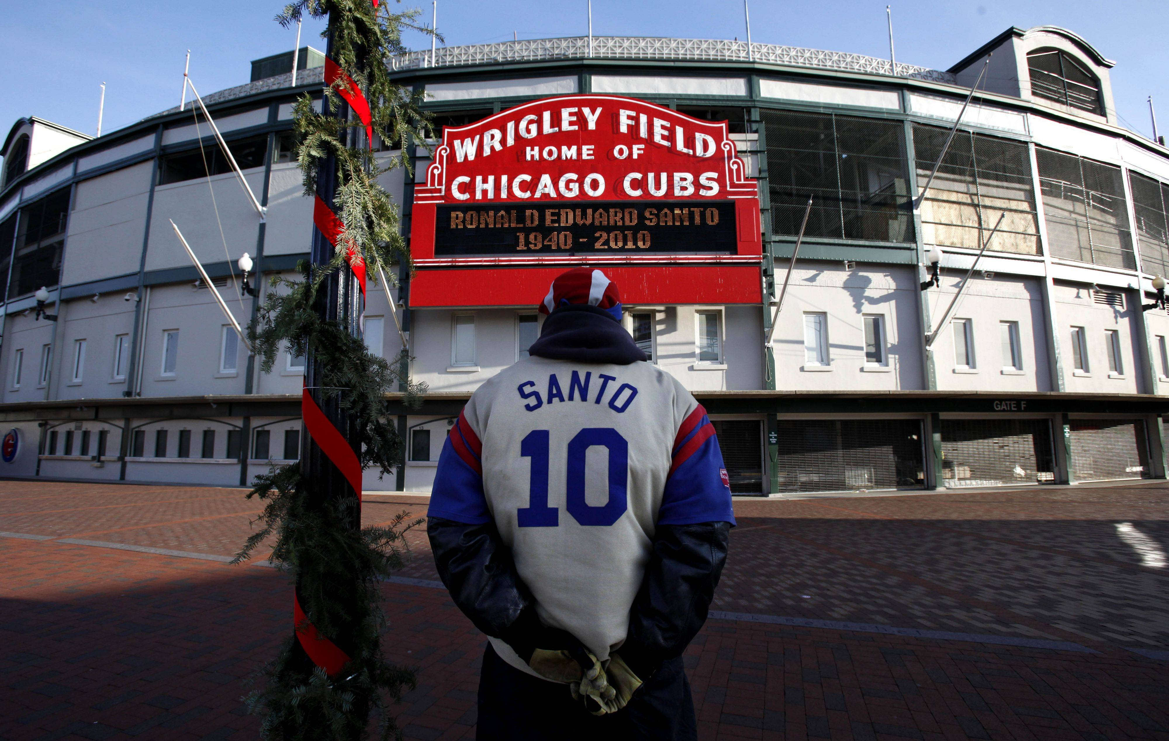 Chicago Cubs' fan Marvin Perez Sr. wears a Ron Santo jacket in front of the Wrigley Field marquee as the news of Santo's death was announced Friday.