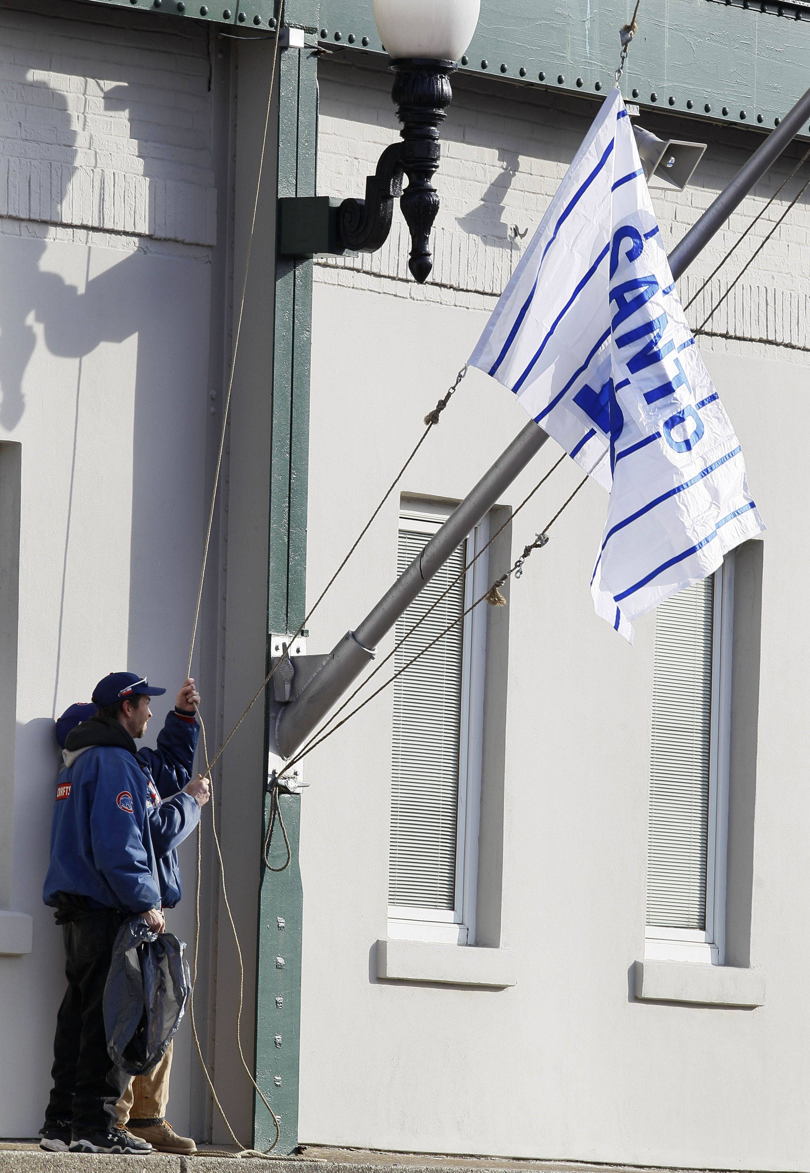Wrigley Field employees raise one of two Ron Santo flags to half mast in front of the stadium after news of the death of one of the Cubs greatest players was announced.
