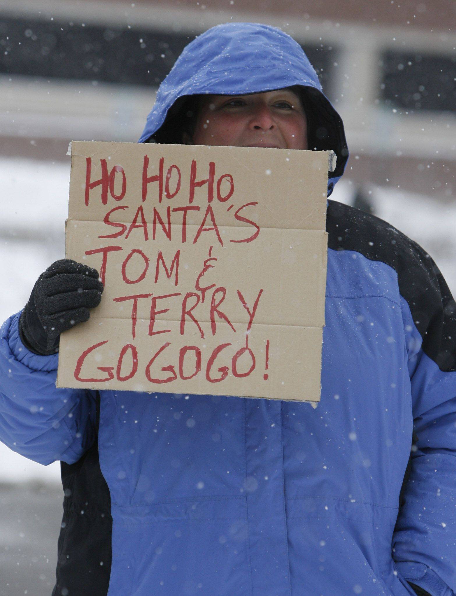 Donna Strum of Elk Grove Village holds a sign urging on a participant in the Santa Sleigh 5K Run in Arlington Heights on Saturday.