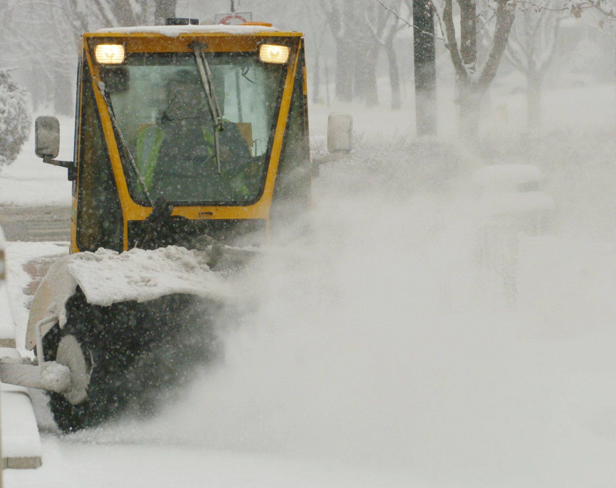 A public works crew clears the sidewalk in front of the Mount Prospect Public Library Saturday morning.