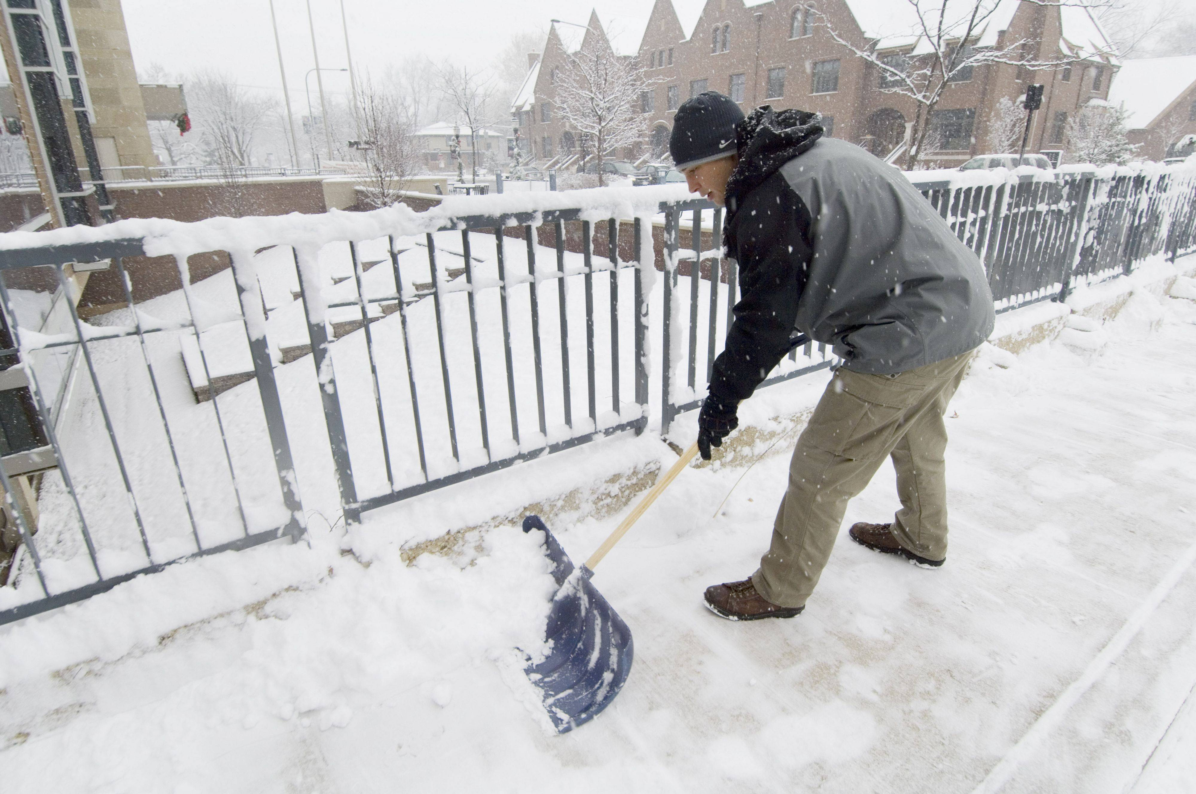 Maintenance worker Russ Jackson shovels the sidewalk adjacent to the Mount Prospect Public Library Saturday morning.