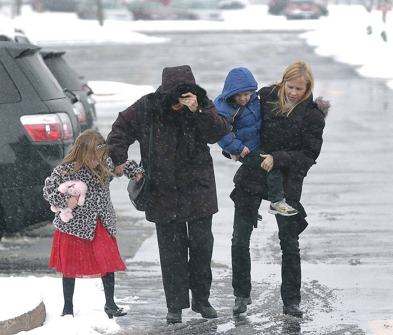 From left, Ashley Harrington, her grandma Pat Marshall, Danny Harrington and mom Jen Harrington make their way through the snowy parking lot on their way to Panera Bread for lunch in Vernon Hills Saturday.