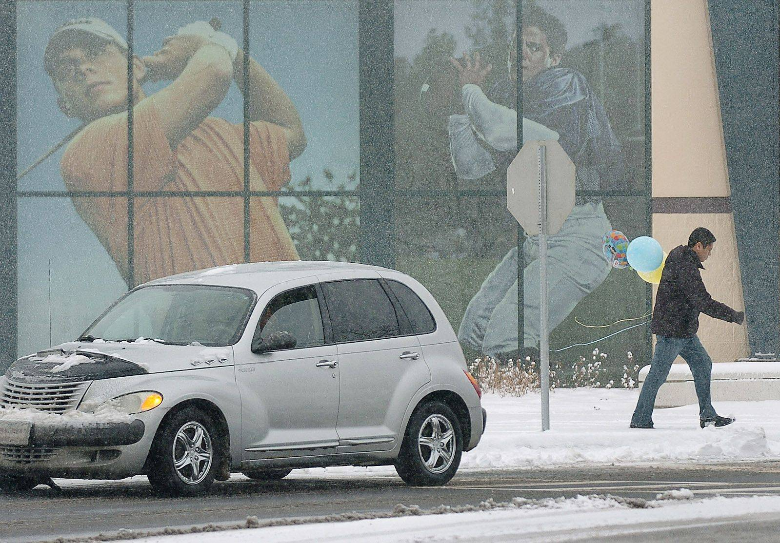A man makes his way Saturday through the snow carrying balloons from Party City in front of Dick's Sporting Goods in Hawthorn Hills Square in Vernon Hills.