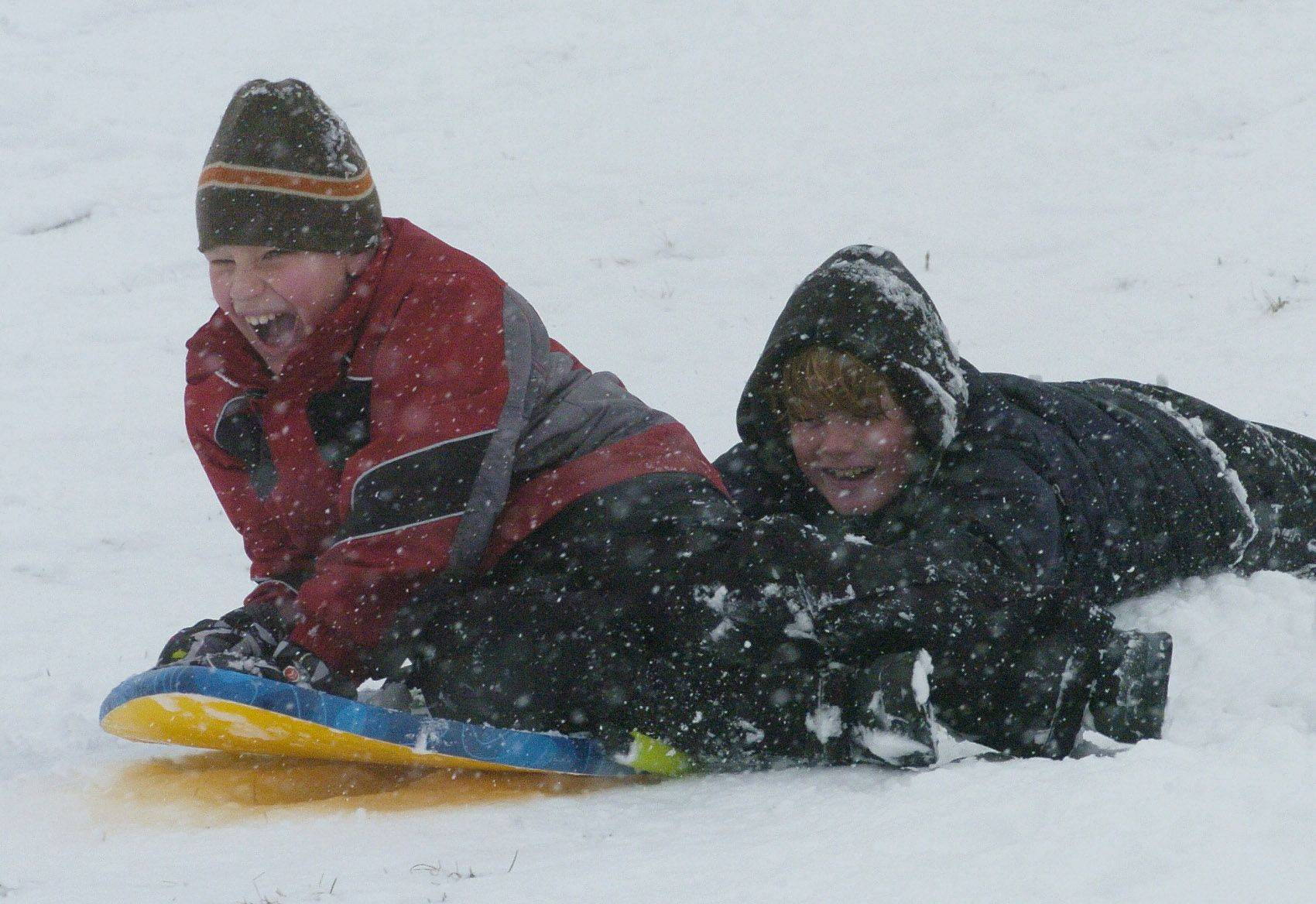 Robert Trapani, 8, and Aiden Brommel, 9, both of Mundelein, sled at Community Park, Mundelein, Saturday.