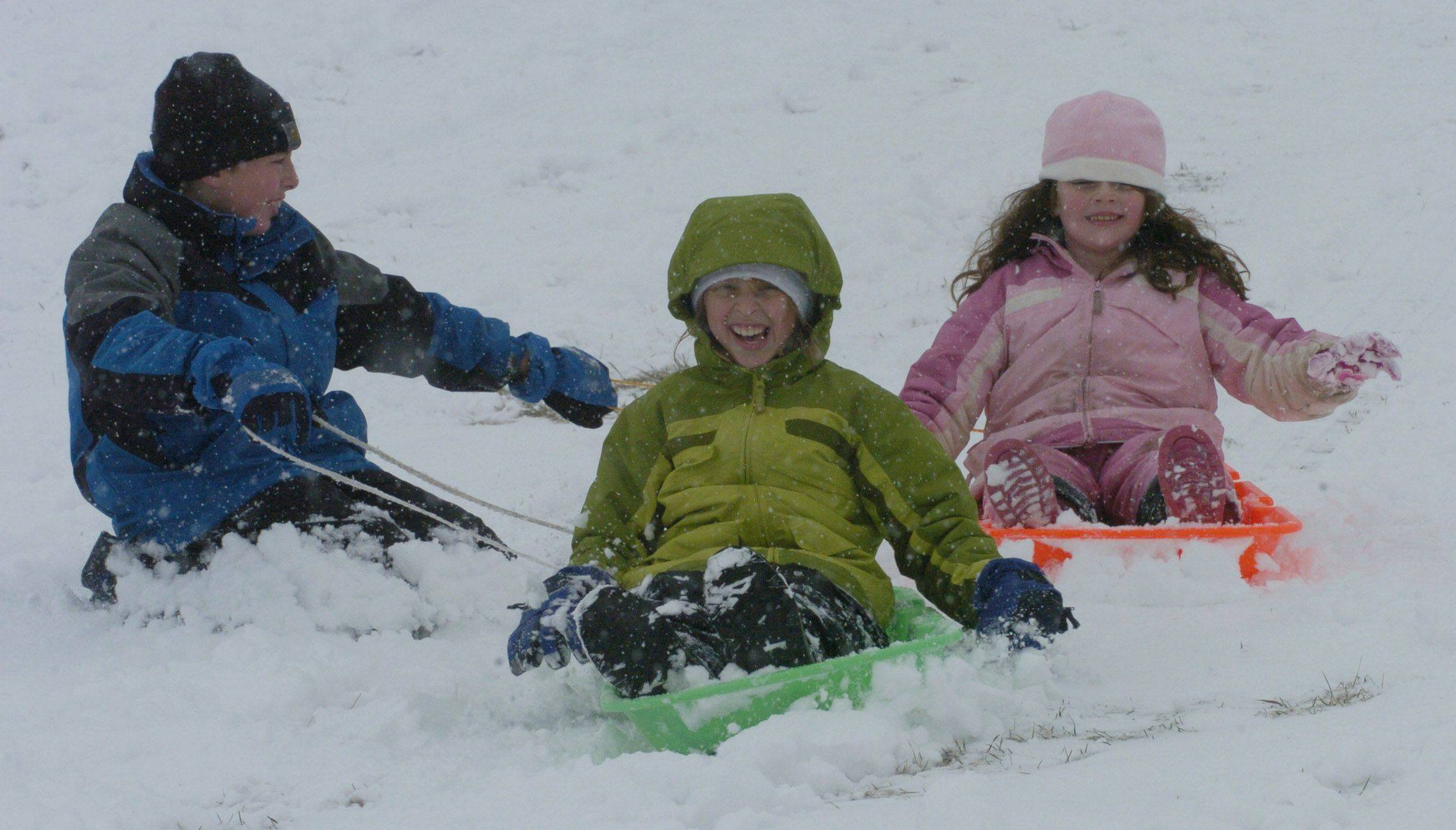 Left to right, Matthew Kieft, 11, of Libertyville, his sister Rebecca, 9, and friend Keely Murphy, 6, of Mundelein sled down the hill at Community Park, Mundelein, Saturday.