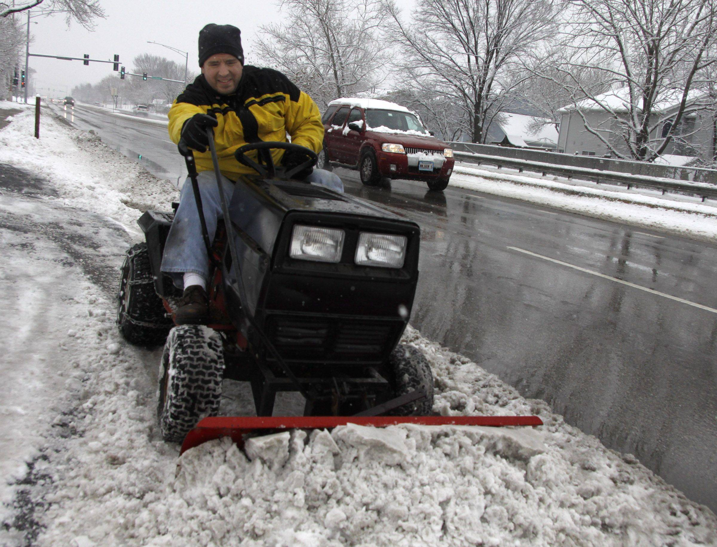 "Matt West plows a stretch of sidewalk in his Glendale Heights neighborhood Saturday. ""I do my two neighbors' driveways, and I plow the sidewalk from Meddowlark to Cardninal every year,"" said West. ""Our little neighborhood is these three houses on Army Trail. We take care of each other."""