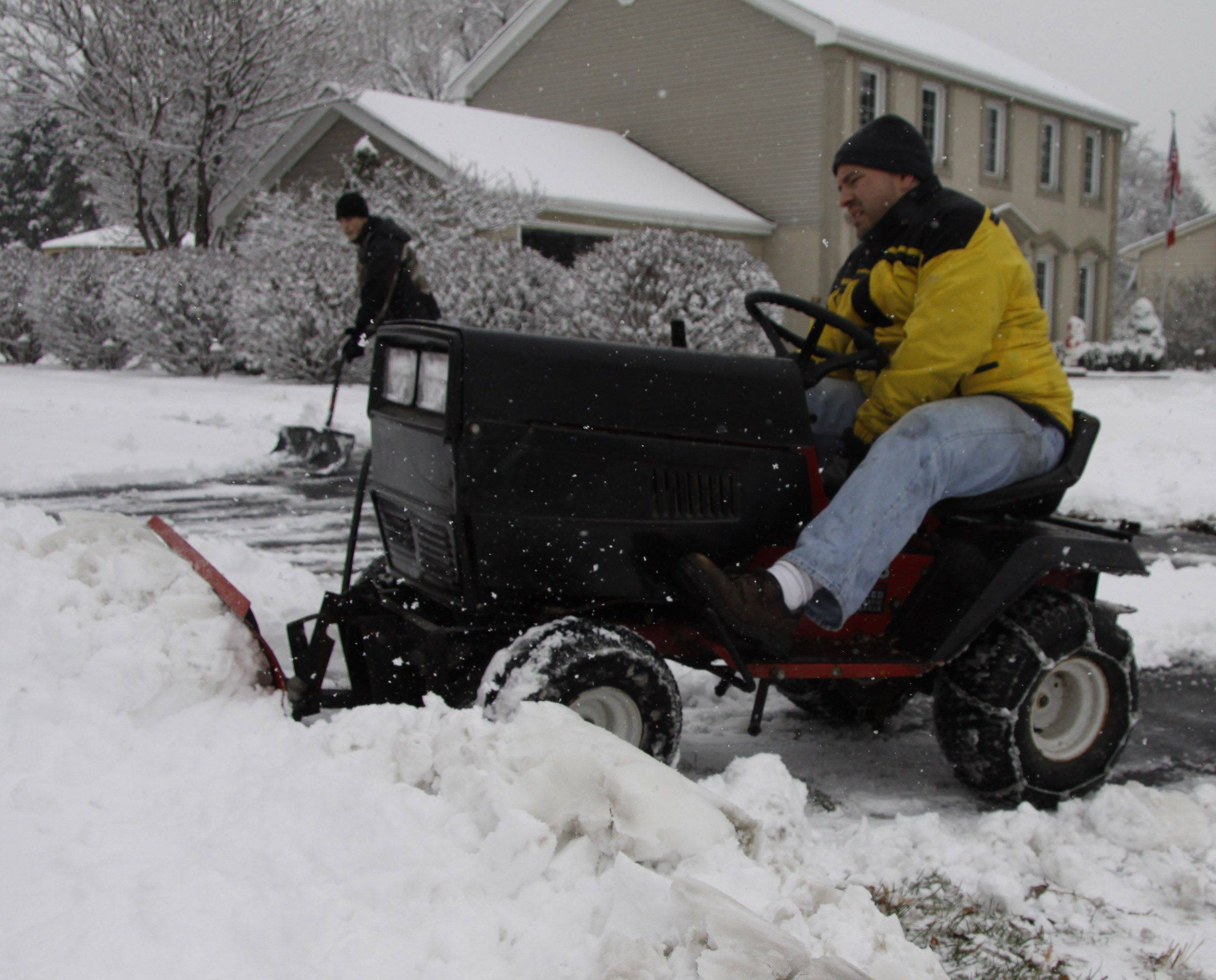"Matt West plows a stretch of sidewalk in his Glendale Heights neighborhood Saturday. ""I do my two neighbors' driveways and I plow the sidewalk from Meddowlark to Cardninal every year,"" said West, whose sons Mike, background, and John joined the effort. ""Our little neighborhood is these three houses on Army Trail. We take care of each other."""
