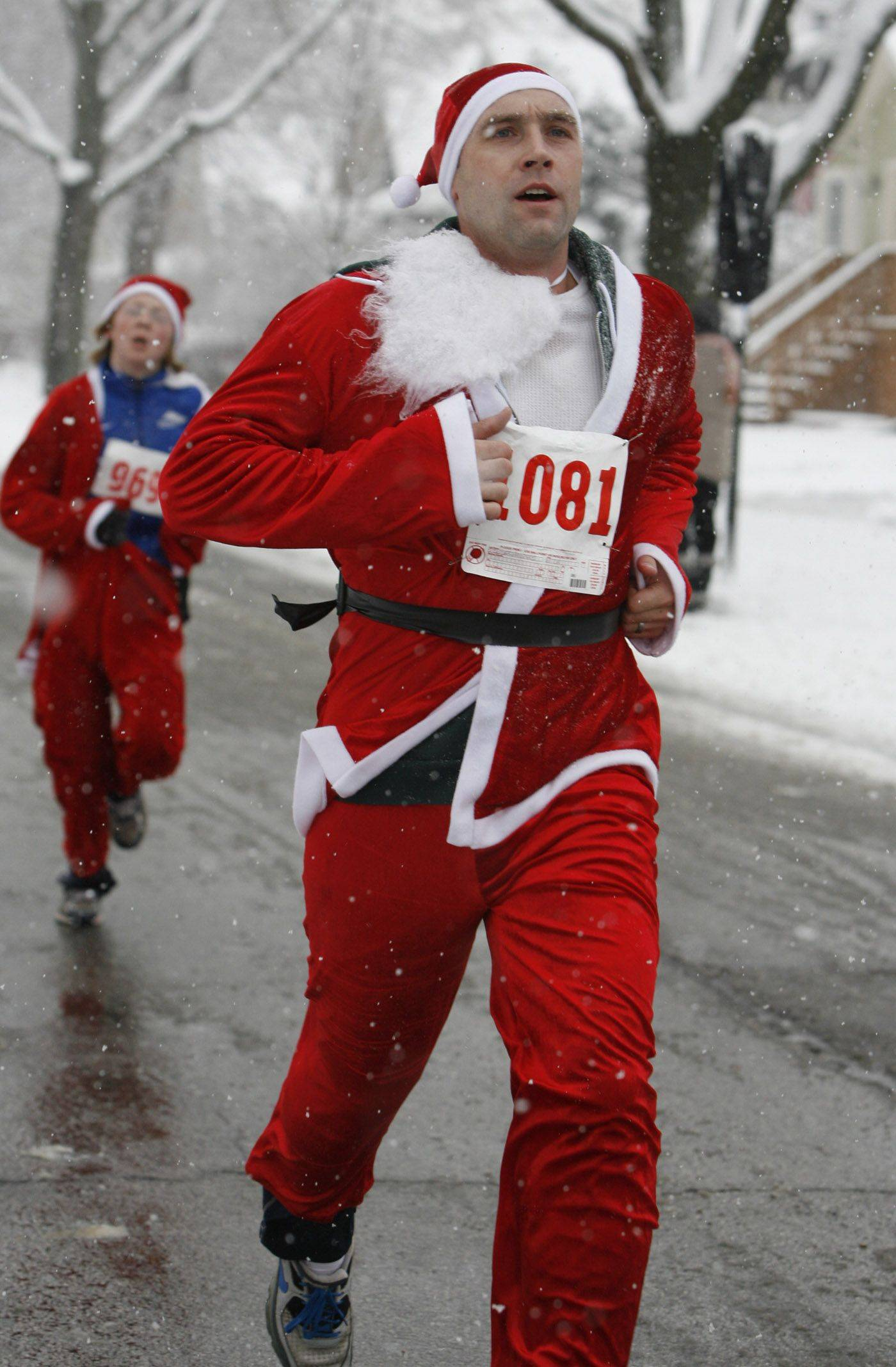 Nick Szczechowski of St. Charles runs in the Arlington Heights Rotary Club´s third annual Rotary Santa 5K run in a snowy downtown Arlington Heights on Saturday.
