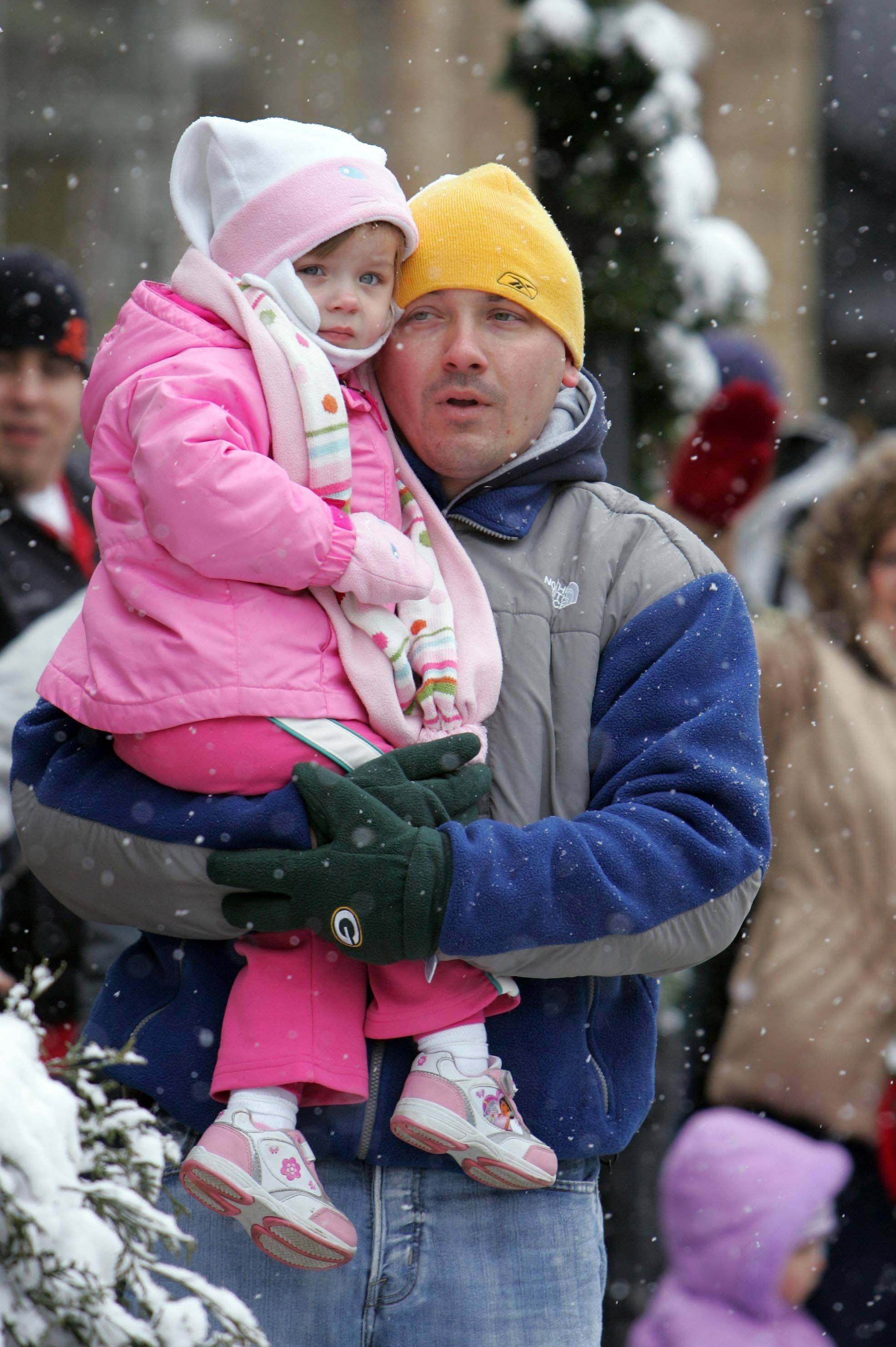 Brian Rohrbacher of Elgin holds his three-year-old daughter Aubrie during the Spirit of Christmas Parade in West Dundee Saturday, December 4, 2010.