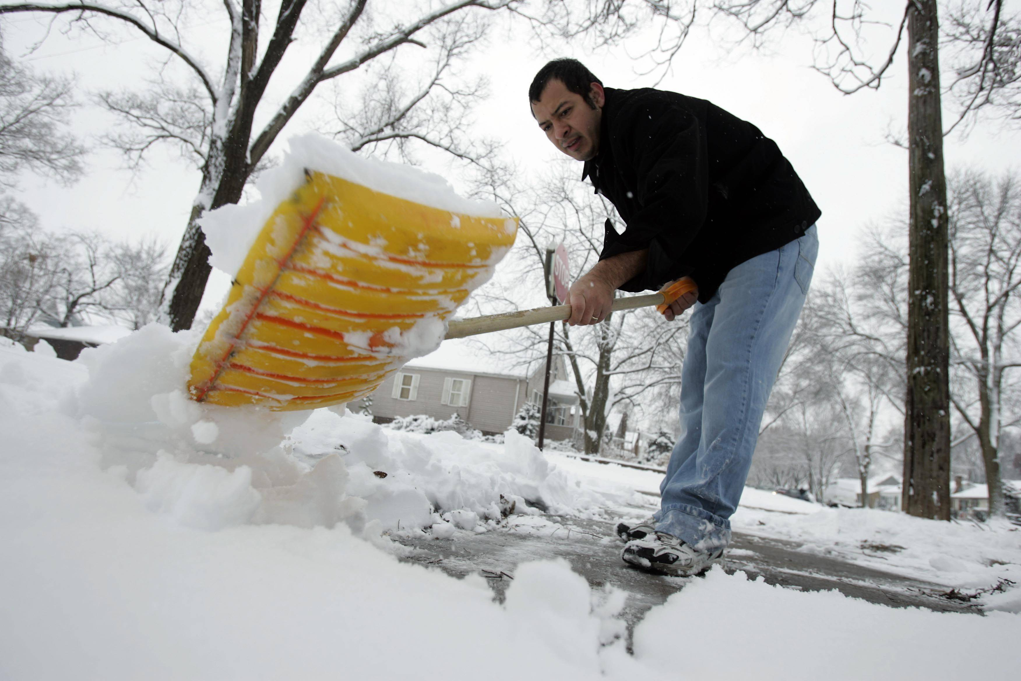 Victor Arguela of Elgin clears his walk during the first big snow in Elgin Saturday, December 4, 2010
