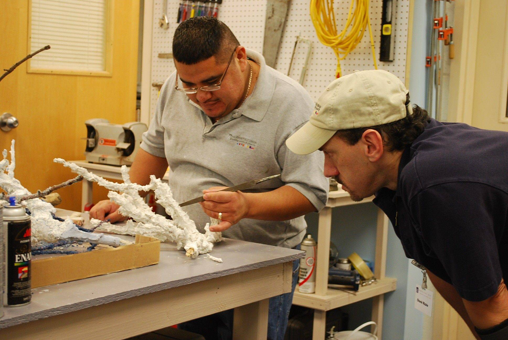 "Francisco Martinez, left, and Chuck Rizzio work closely on a coral reef display that is part of the ""Under the Sea"" exhibit at the Waukegan Public Library."