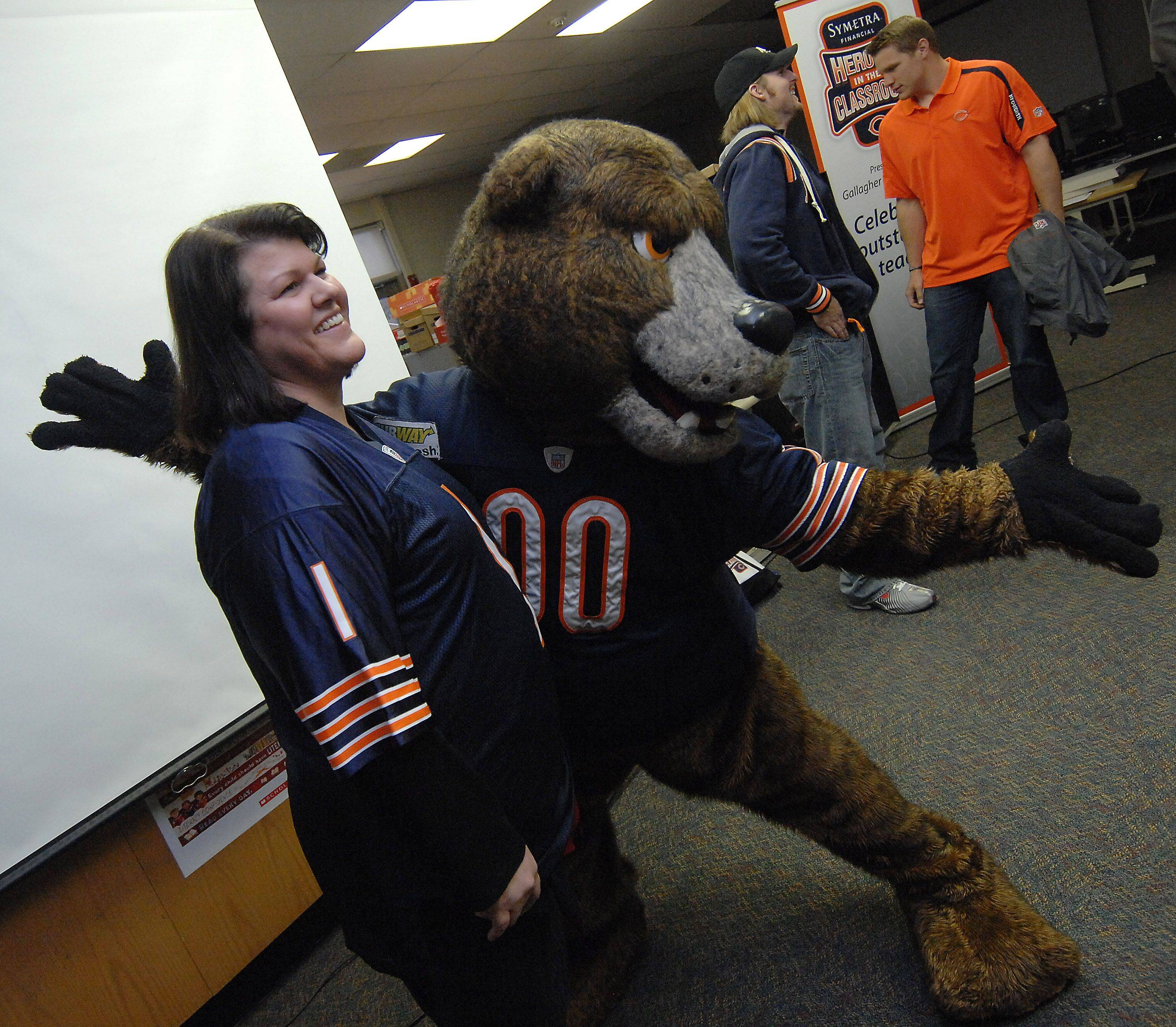 Staley the Chicago Bears mascot presents River Trails Middle School Heroes in the Classroom winner Mrs. Jennifer Ritchie, eighth-grade teacher of Lombard to the entire eighth-grade student body on Tuesday in Mt. Prospect.